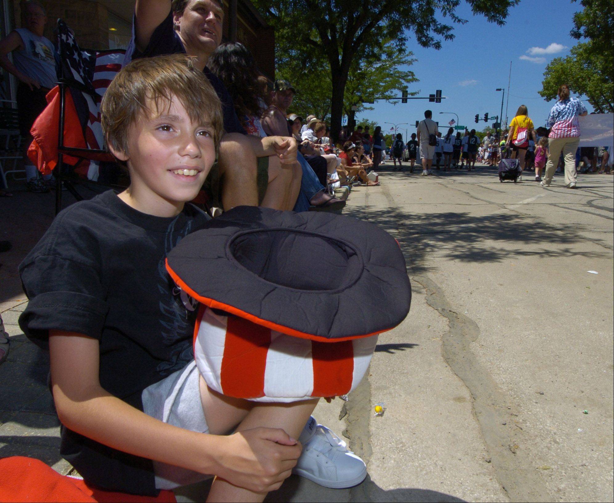 Garrett Hornak, 9, of Kildeer holds his hat out for candy during the Mount Prospect Fourth of July parade Monday.