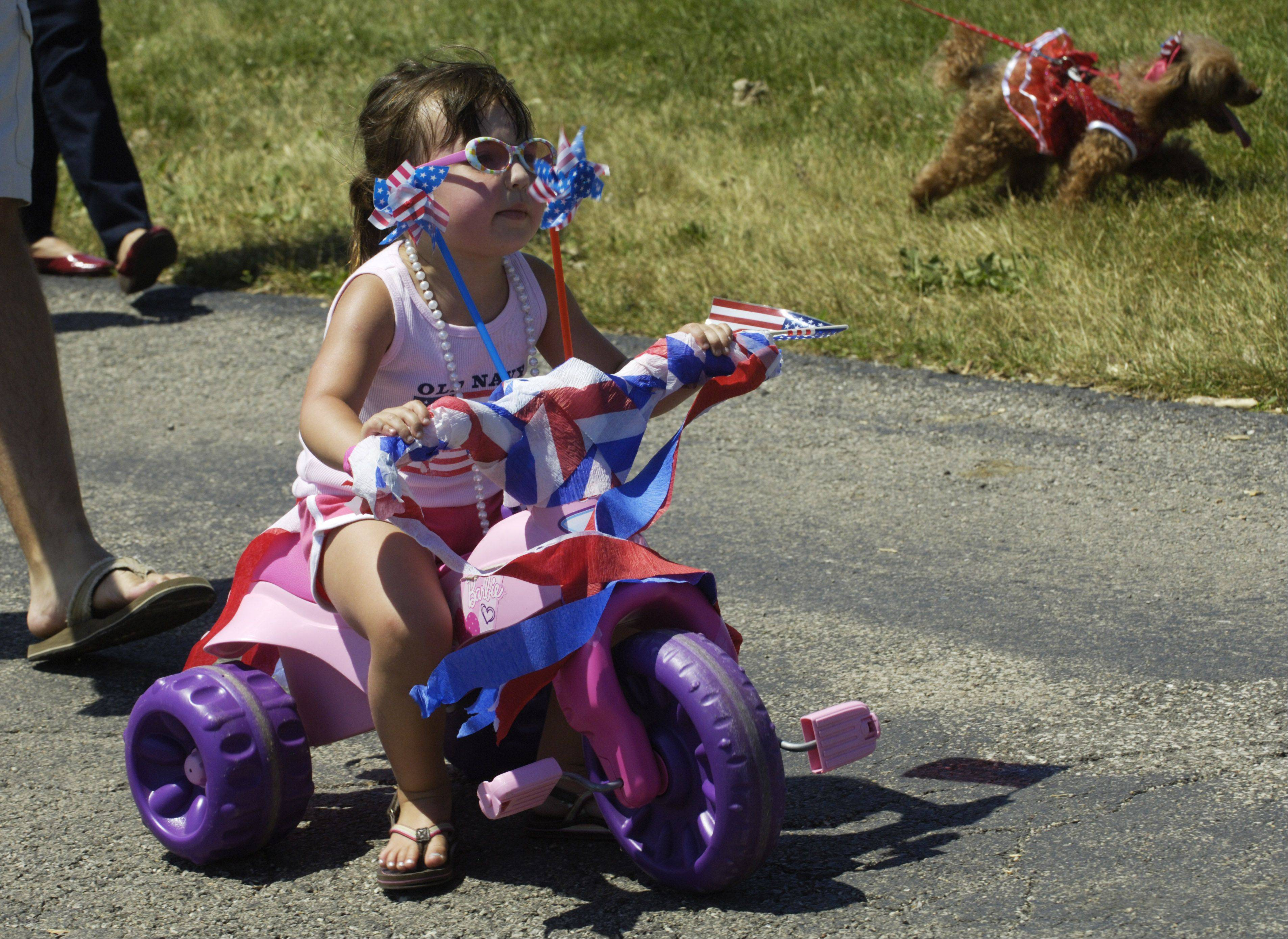 Taylor Meyer, 3, of Wheeling rides her three-wheeler in the Sis Boom Bike and Pet Parade during the Wheeling Park District 50th anniversary/Independence Day Celebration.