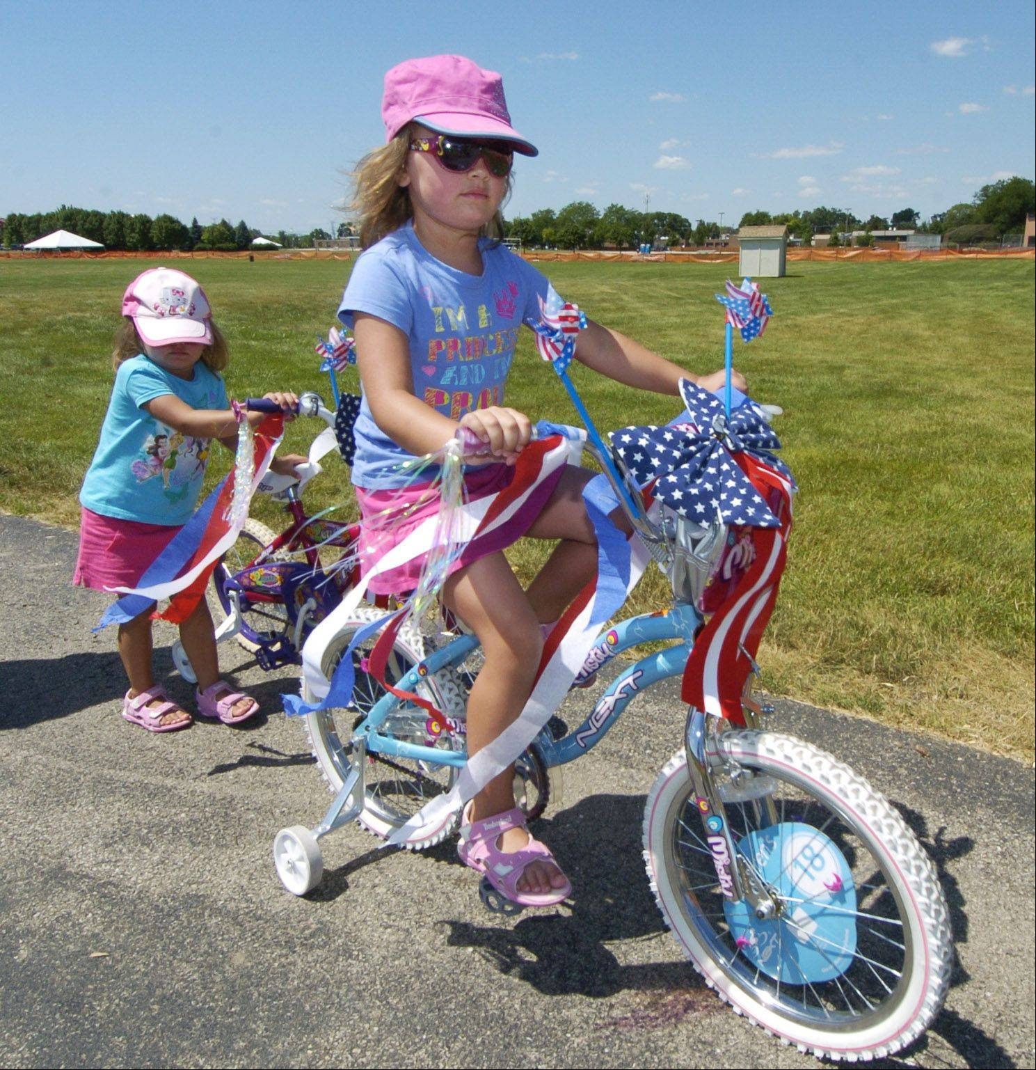 Julia Machowska, 5, rides her bike while her sister, Emily, 3, pushes hers, while participating in the Sis Boom Bike and Pet Parade during the Wheeling Park District 50th anniversary/Independence Day Celebration.
