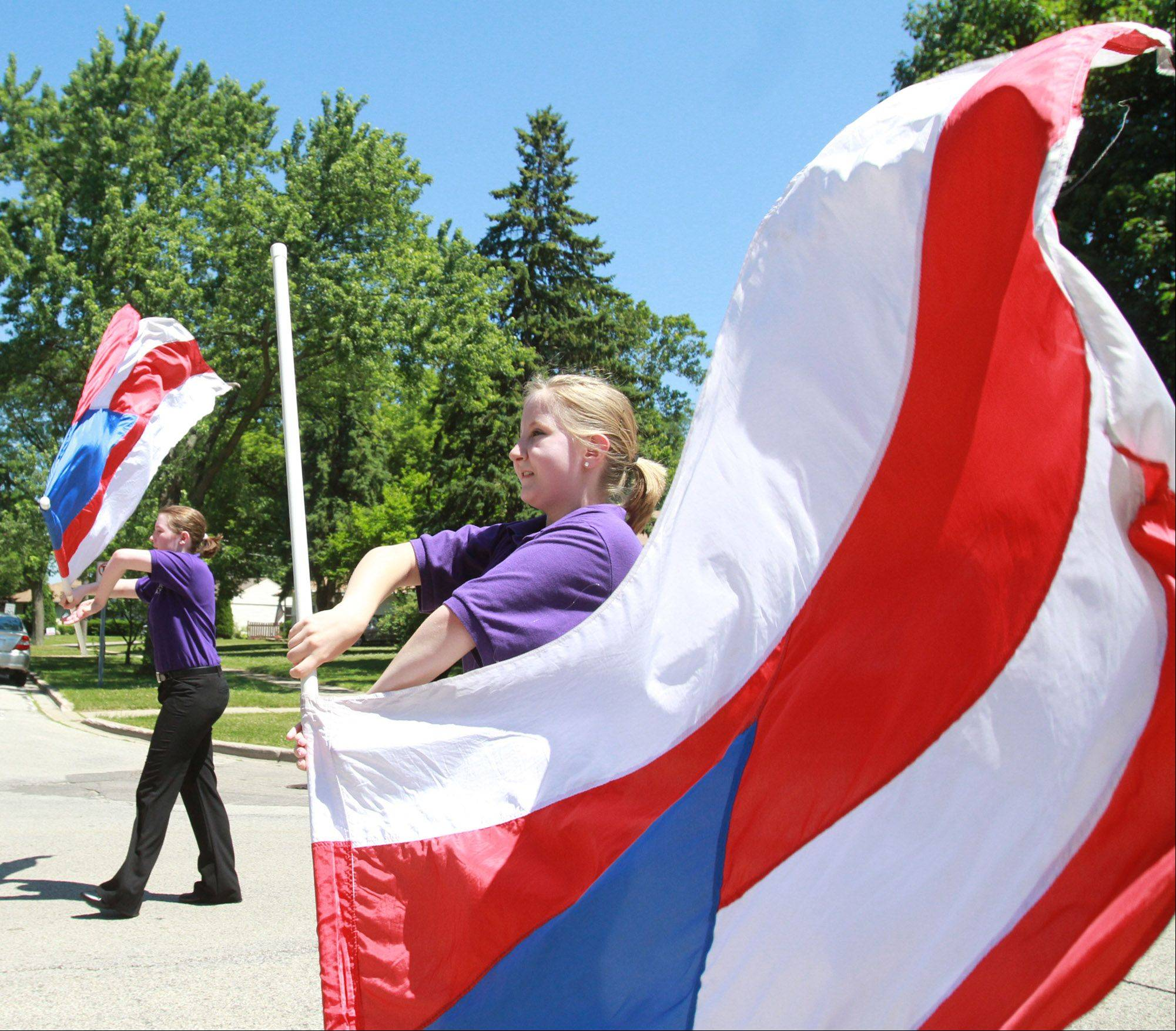 Rolling Meadows High School floggers march in front of the school's marching band in the Rolling Meadows Fourth of July parade on Monday.