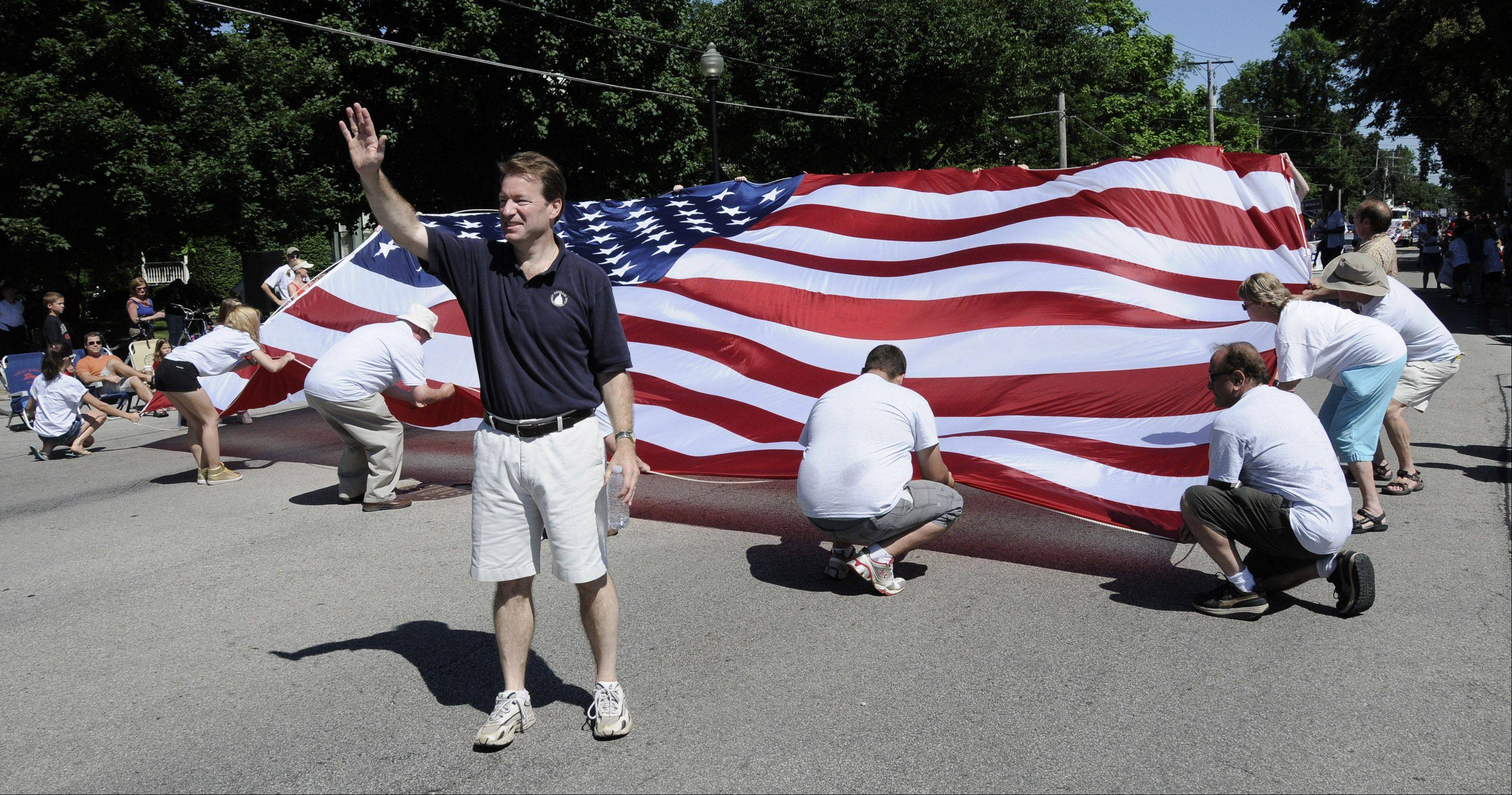 One of many politicians marching Monday, in Wheaton's Independence Day parade is Republican Congressmen Peter Roskam, who walked in front of a huge American flag carried by his friends and supporters.