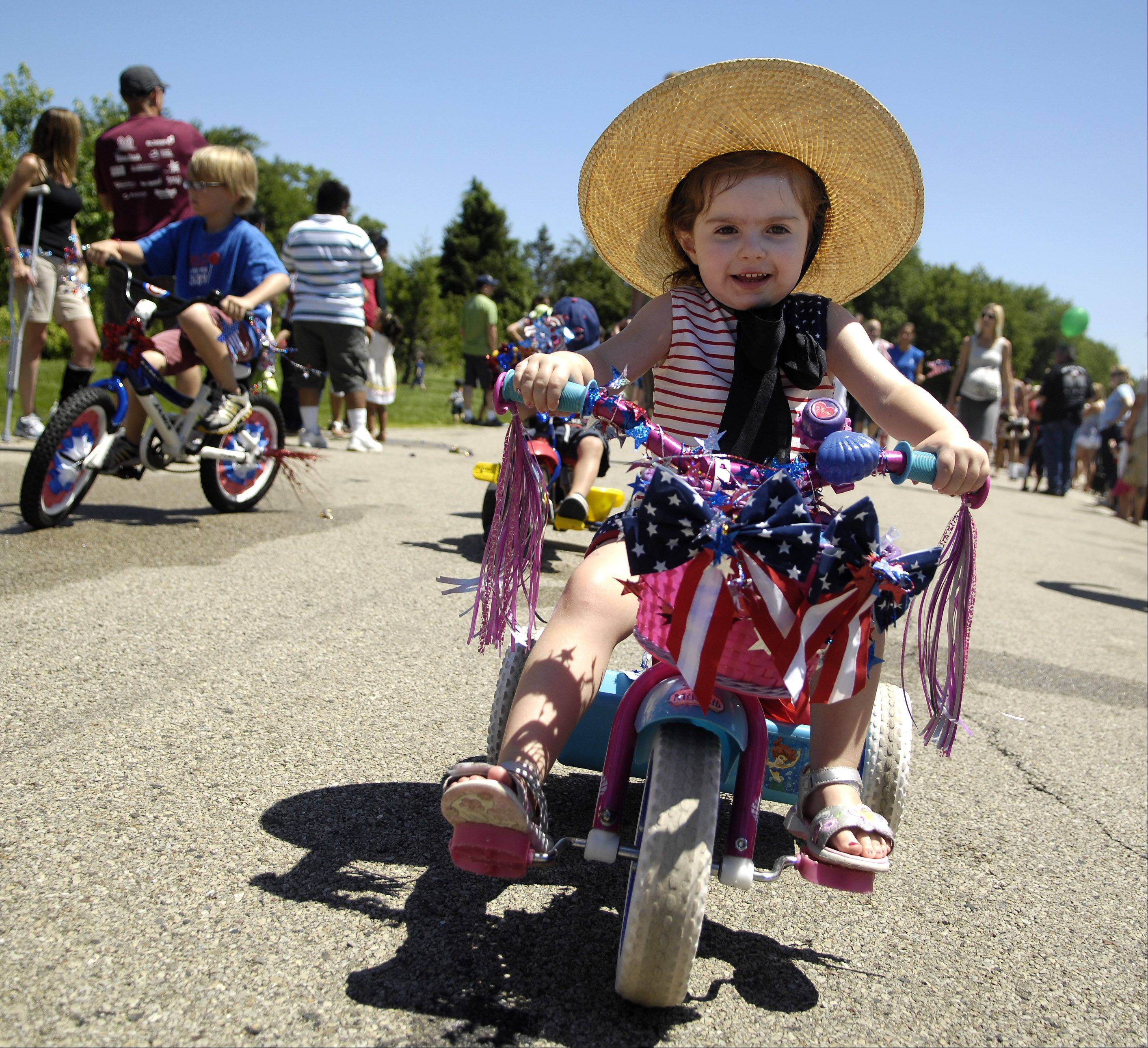 3-year-old Chloe Coffey of Lake in the Hills rides her decorated trike along the route during Sleepy Hollow's Fourth of July parade Monday. Her grandparents live in nearby West Dundee.