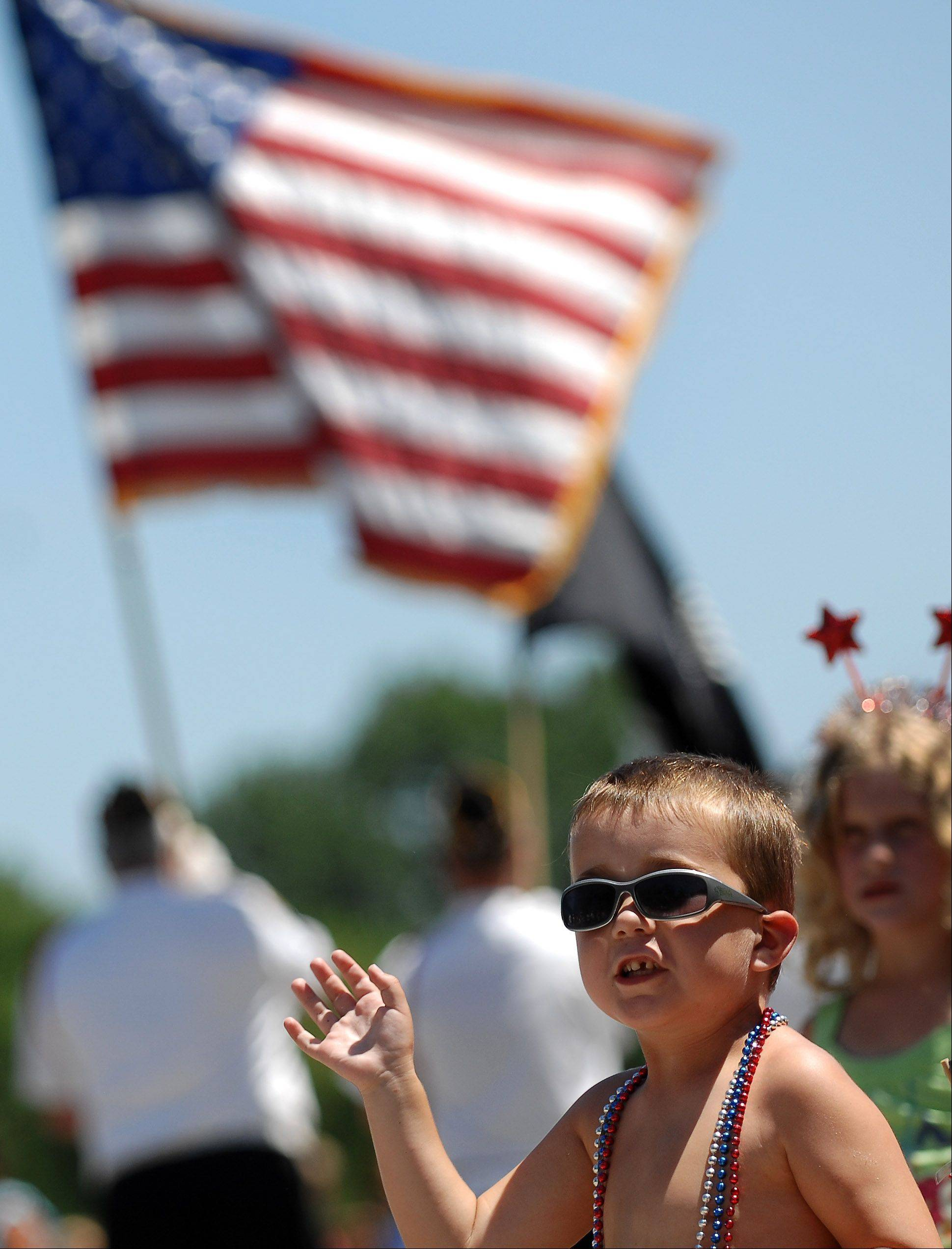 5-year-old Jake Kenefick of West Dundee waves to a police car as it passes during Sleepy Hollow's Fourth of July parade Monday.