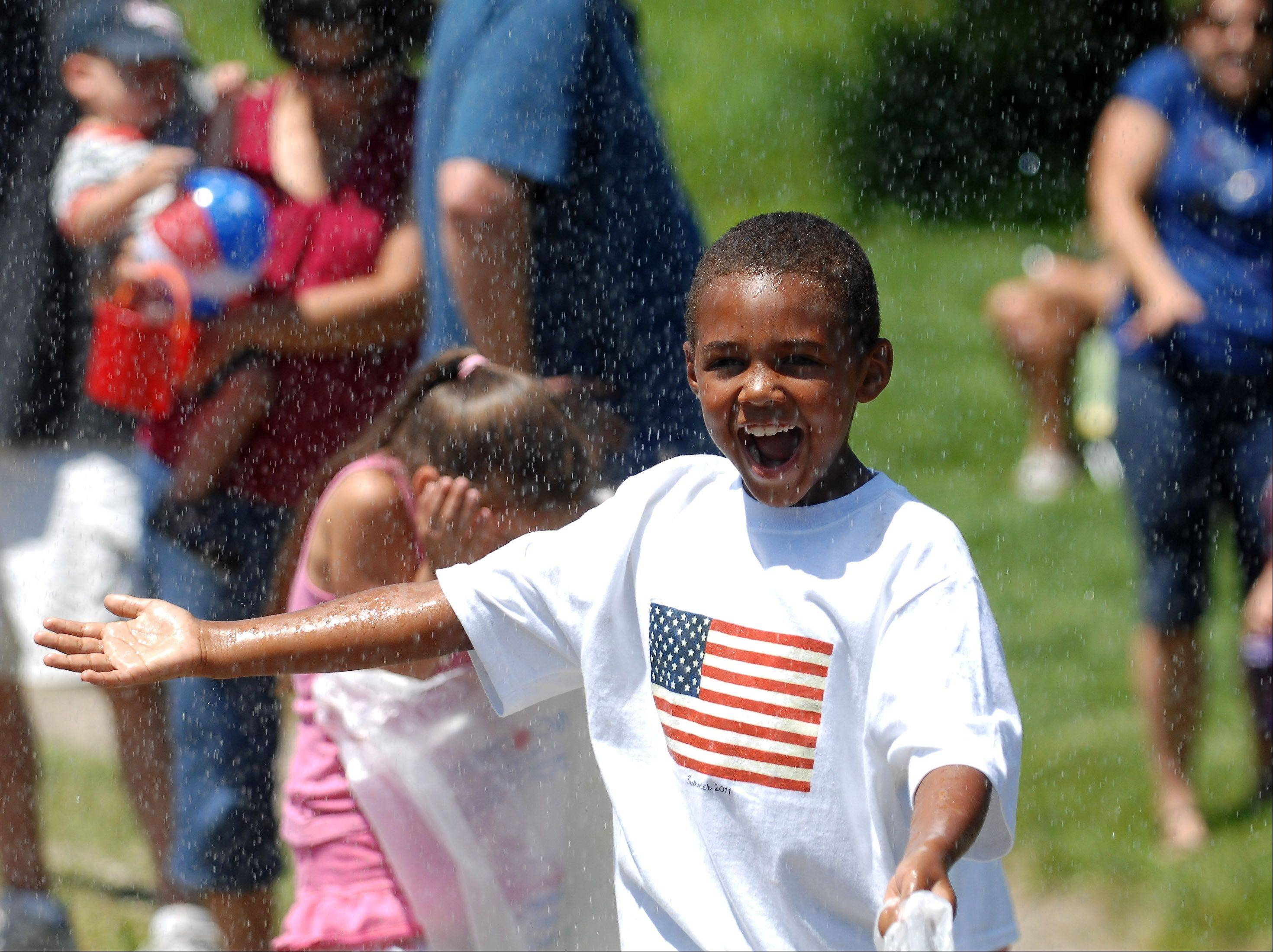 While others scurry or hide, T.J. Stoutemire, 7, of West Dundee embraces the cool shower sprayed on the crowd by a Rutland-Dundee fire truck during Sleepy Hollow's Fourth of July parade Monday.
