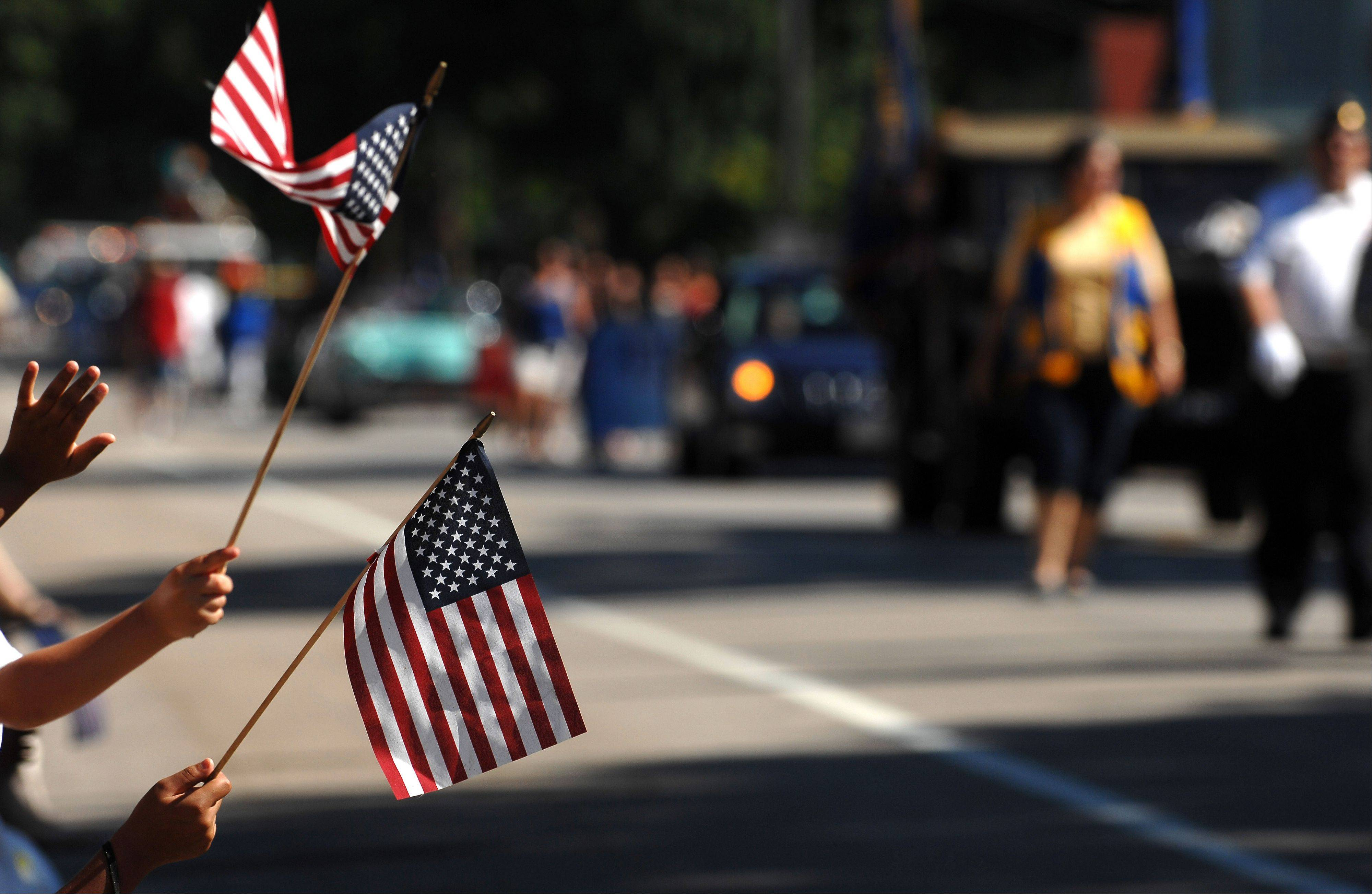 Spectators wave hands and flags during Elgin's Fourth of July parade Monday.
