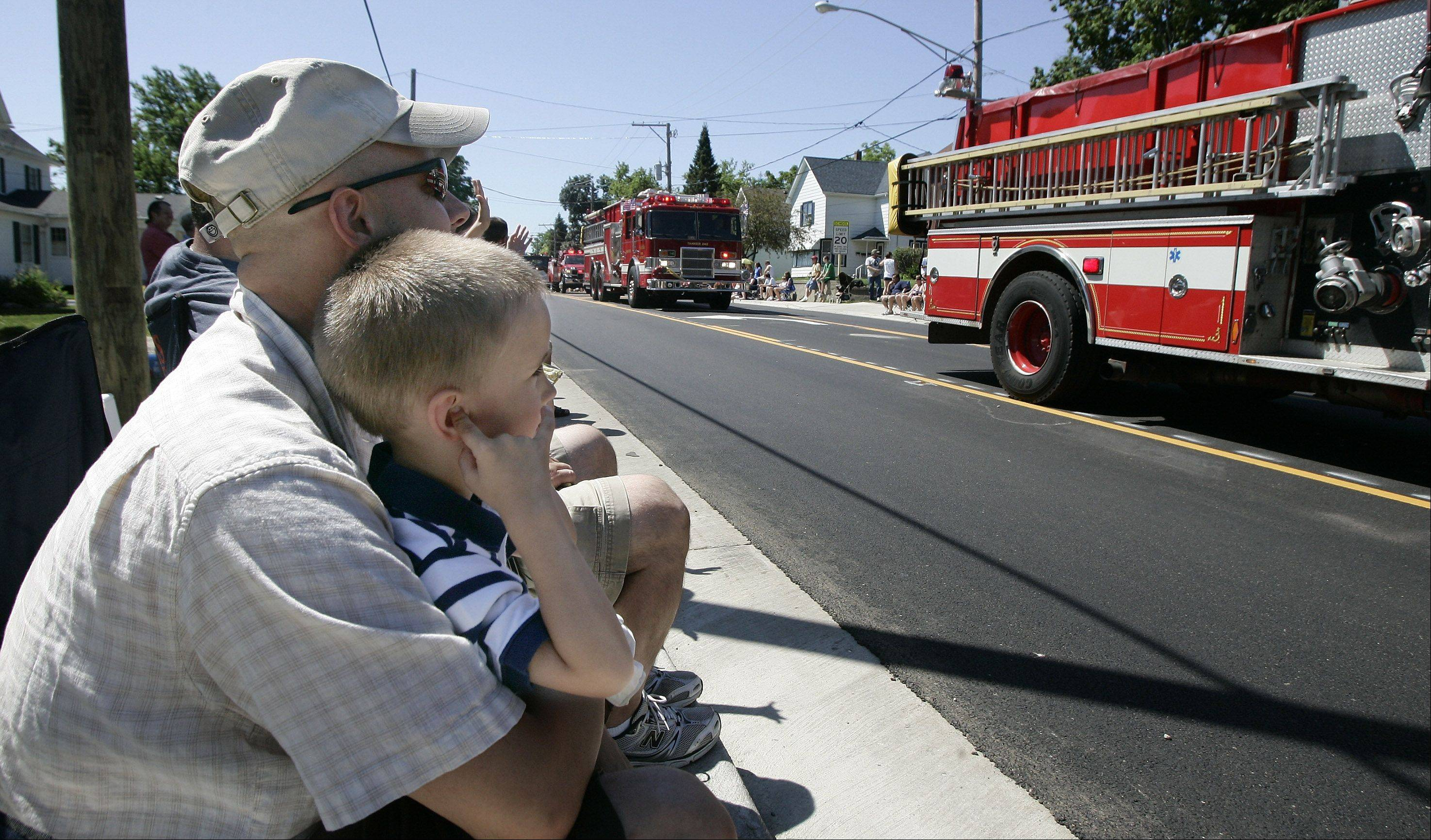 Adam Spisak, 4, of Lake Villa covers his ears as he watches the fire engines go by with his dad, Joe, during the Antioch Fourth of July parade Monday.