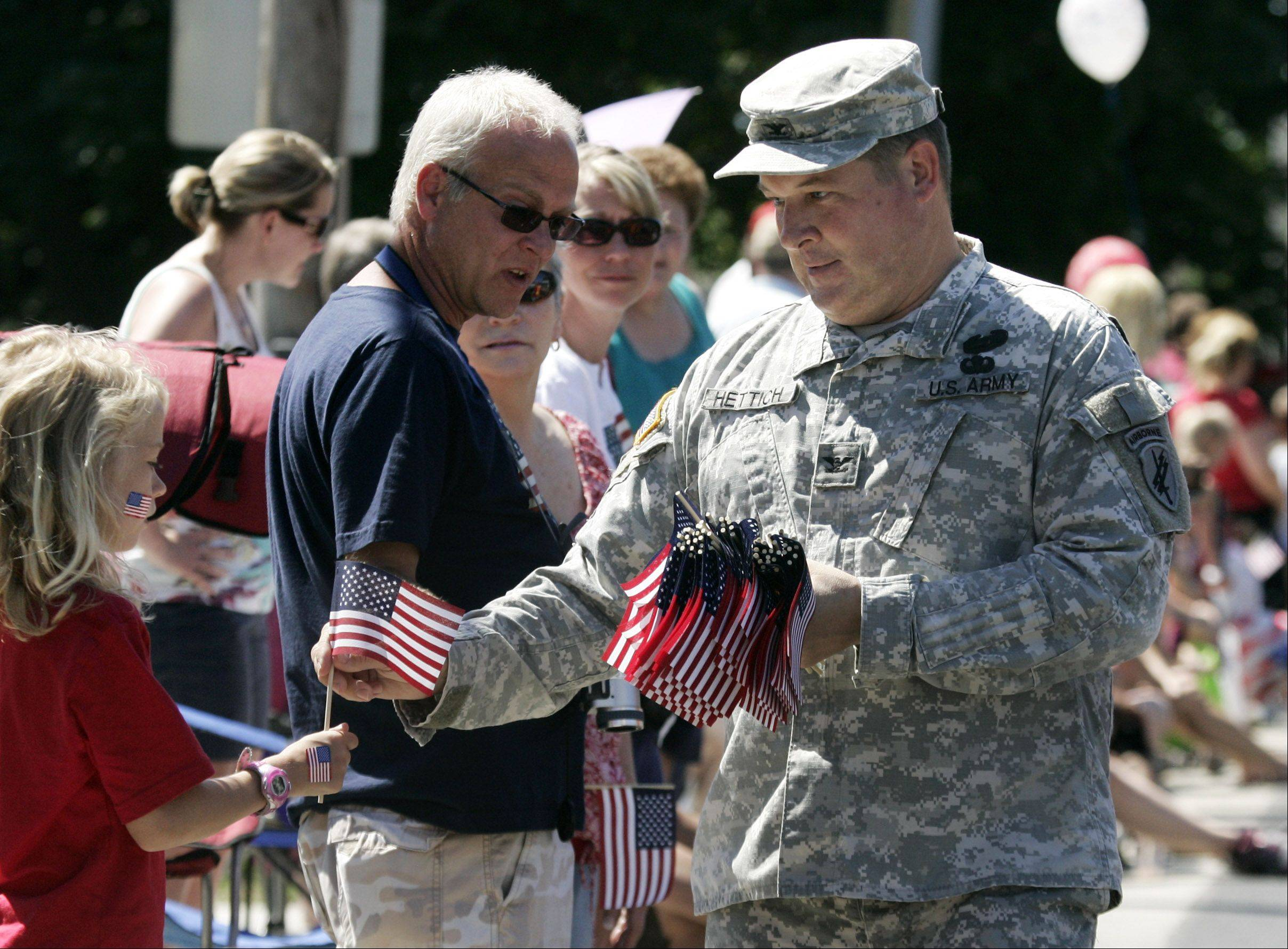 U.S. Army Col. Paul Hettich hands out flags during the Antioch Fourth of July parade Monday. Hettich has spent three tours in Iraq and is scheduled to go to Afghanistan.