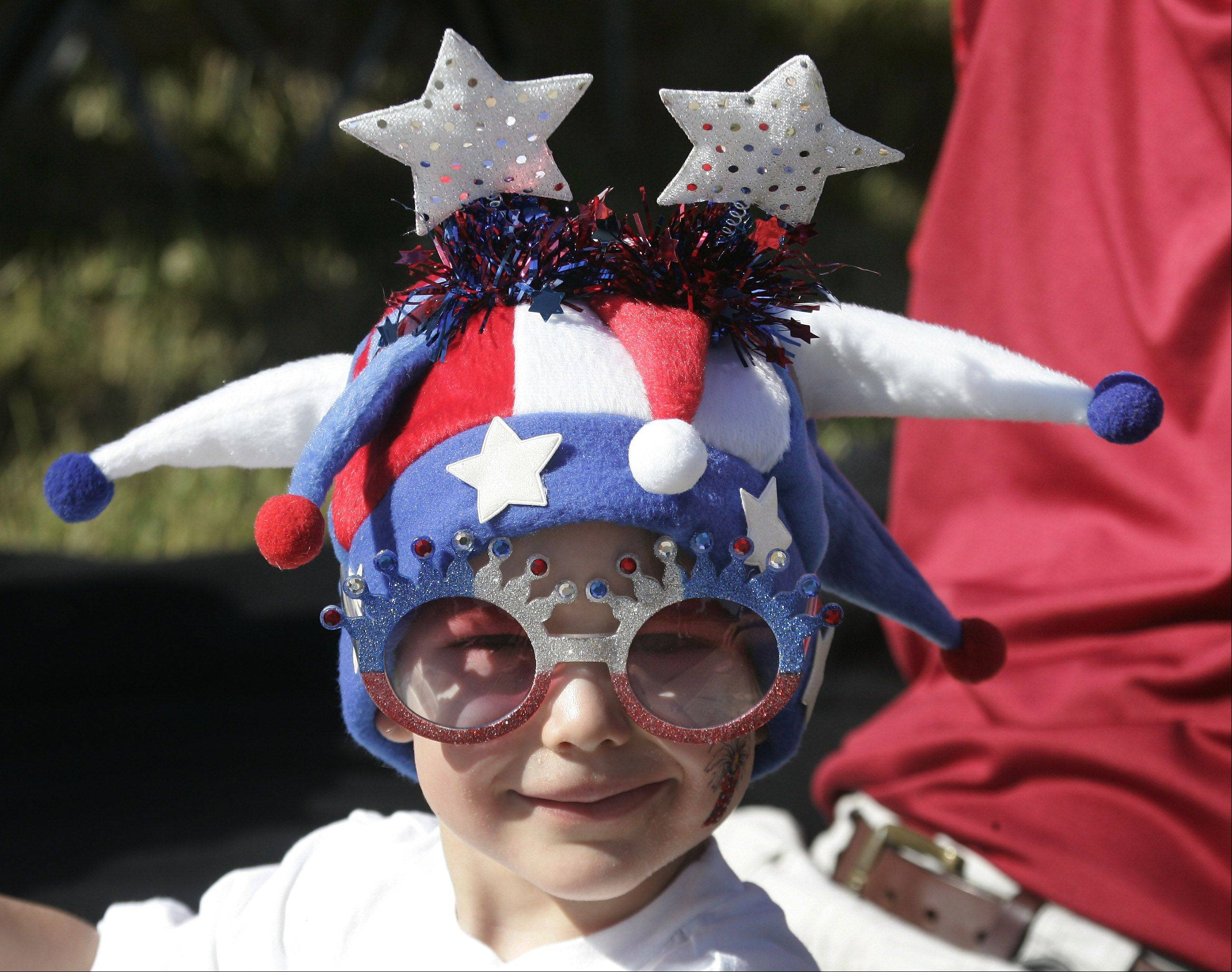 Caden Longdon, 4, watches the parade dressed in holiday clothes along Deerpath Drive during the Vernon Hills Fourth of July parade Monday.