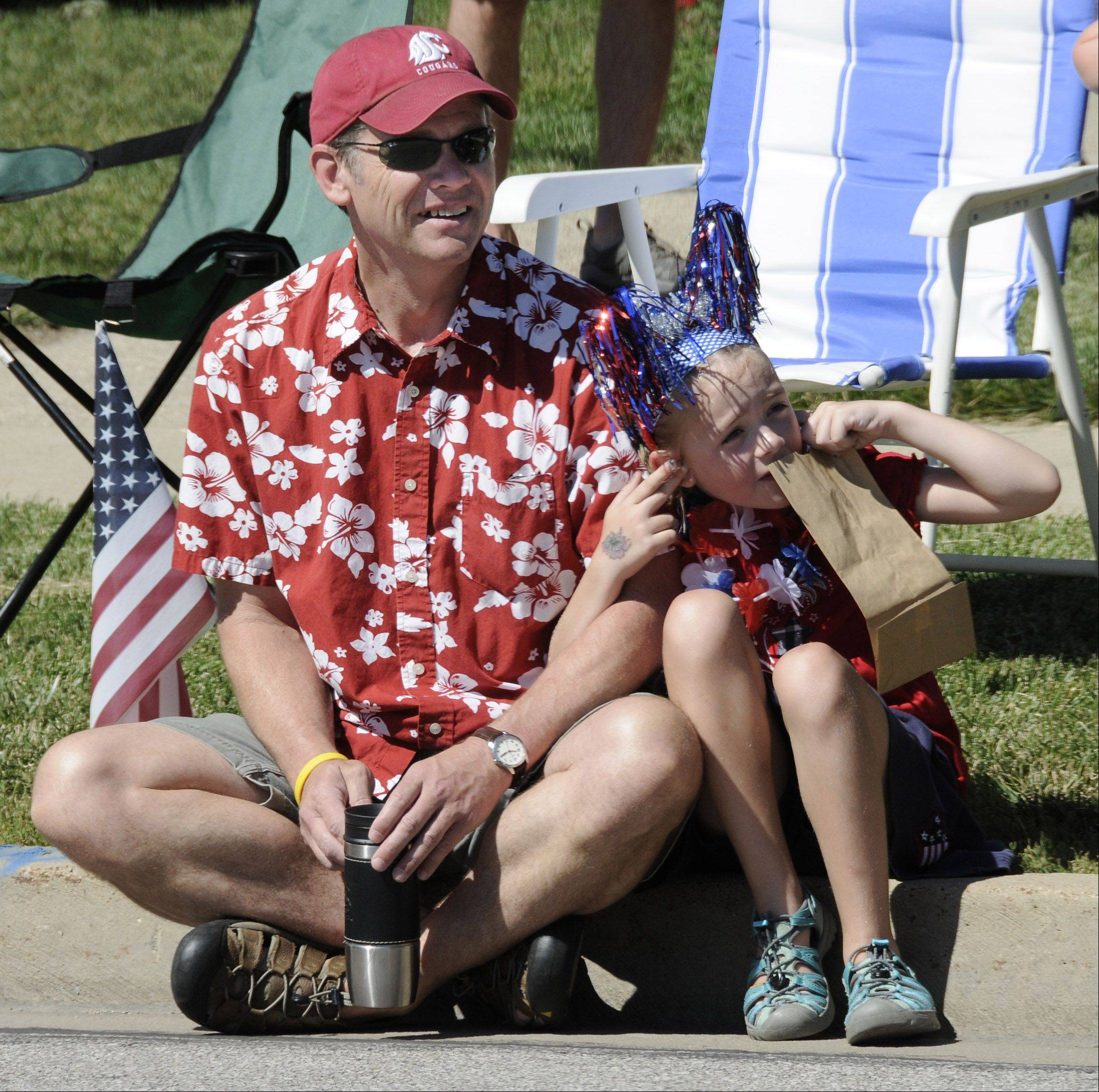 Glenn Martin watches while his daughter Leah covers her ears from the racket of the Wheaton Fire Department's sirens at Wheaton's Independence Day parade.