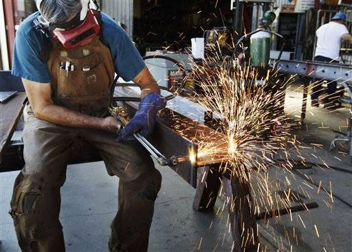 In this July 1, 2011 photo, John Rosas, an employee with the metal works factory Wizard of Metals, cuts steel in San Francisco. Businesses requested more airplanes, autos, and oil drilling equipment in May. The increase in factory orders suggests supply disruptions stemming from the Japan crisis are fading.