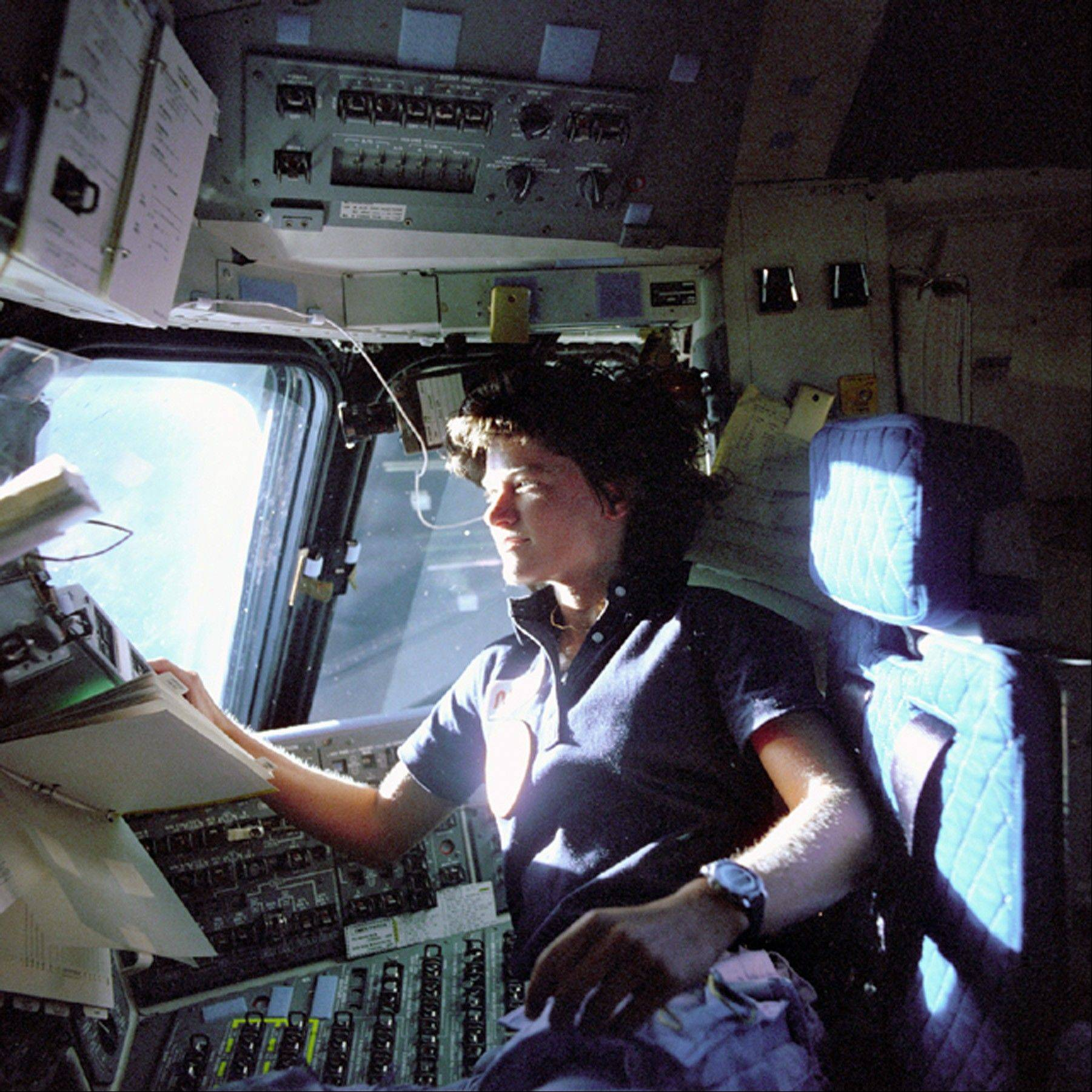 Astronaut Sally Ride, a specialist on shuttle mission STS-7, monitors control panels from the pilot's chair on the shuttle Columbia flight deck. Ride became America's first woman in space when Columbia launched June 18, 1983.