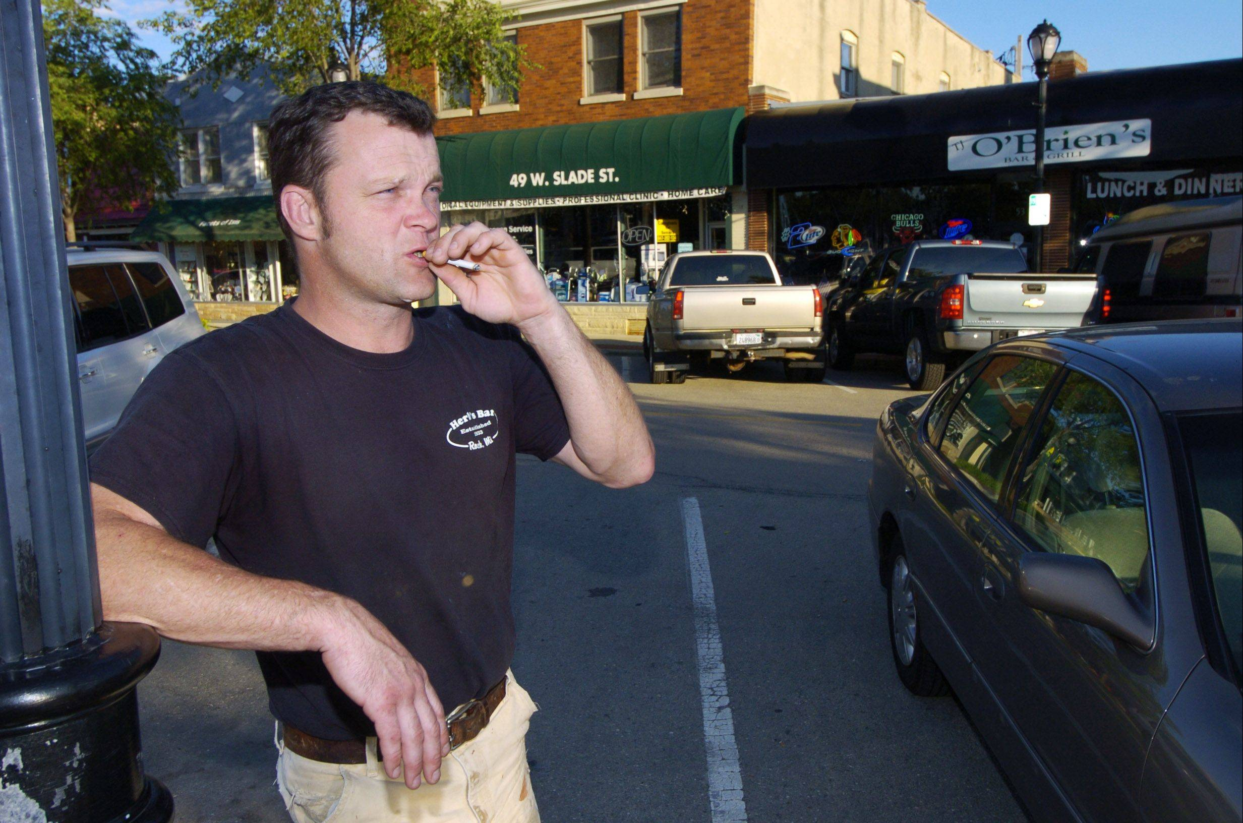 Michael Hane of Palatine smokes a cigarette while standing across the street from T.J. O'Brien's in Palatine.