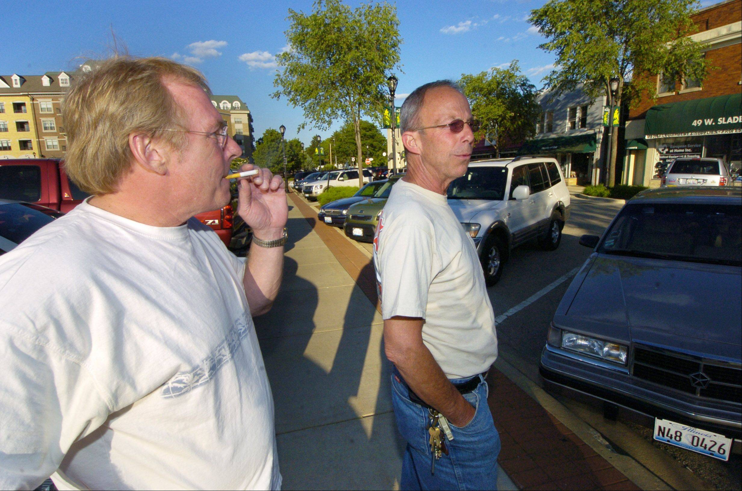 Michael Casey, left, and Kevin O'Neal, both of Palatine, chat while smoking across the street from T.J. O'Brien's in Palatine.