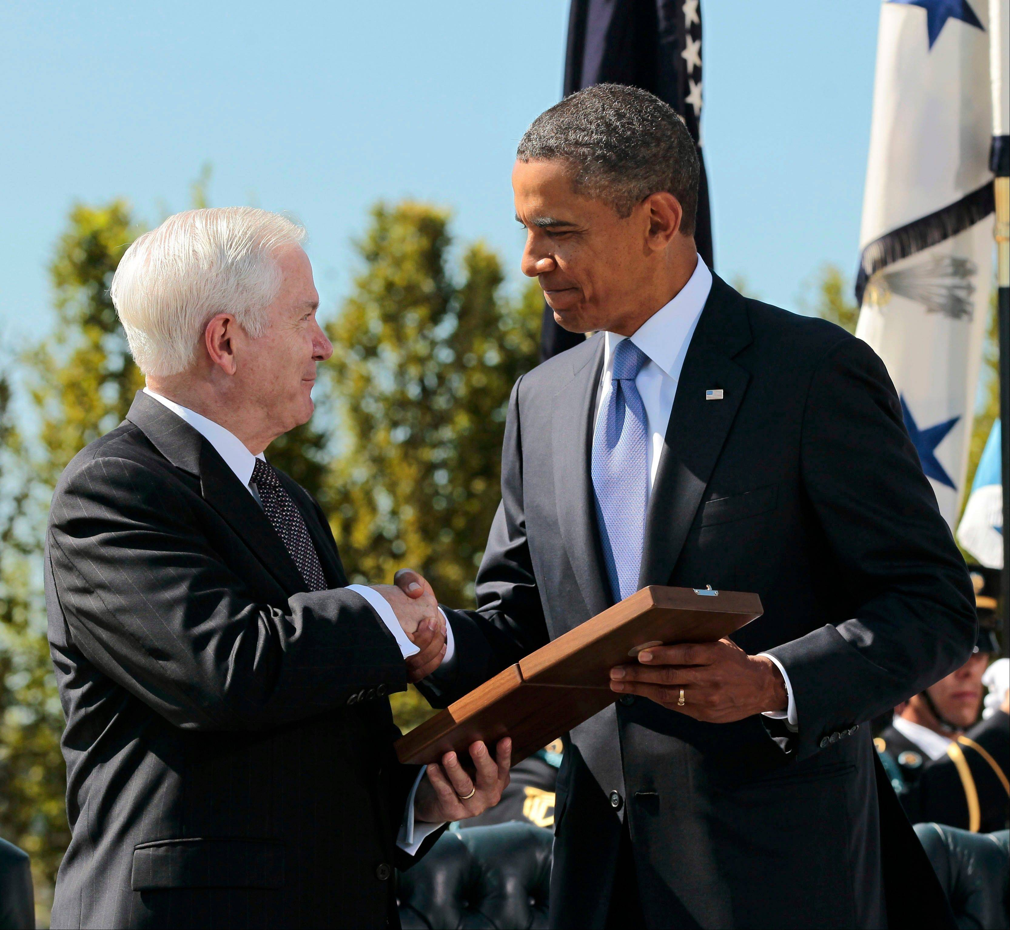 President Barack Obama presents the Presidential Medal of Freedom to retiring Defense Secretary Robert Gates during an Armed Forces Farewell Tribute, Thursday, June 30, 2011, at the Pentagon.