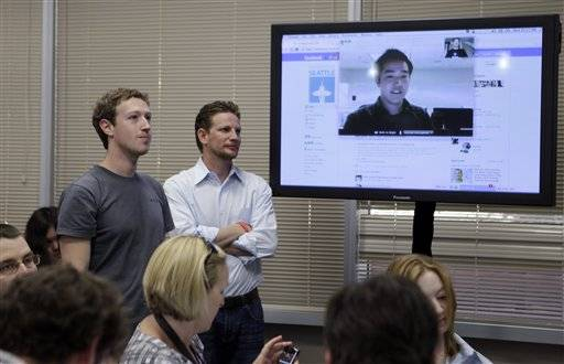 Facebook CEO Mark Zuckerberg, left, watches a demonstration of Video Chat during an announcement at Facebook headquarters in Palo Alto, Calif., Wednesday, July 6, 2011.