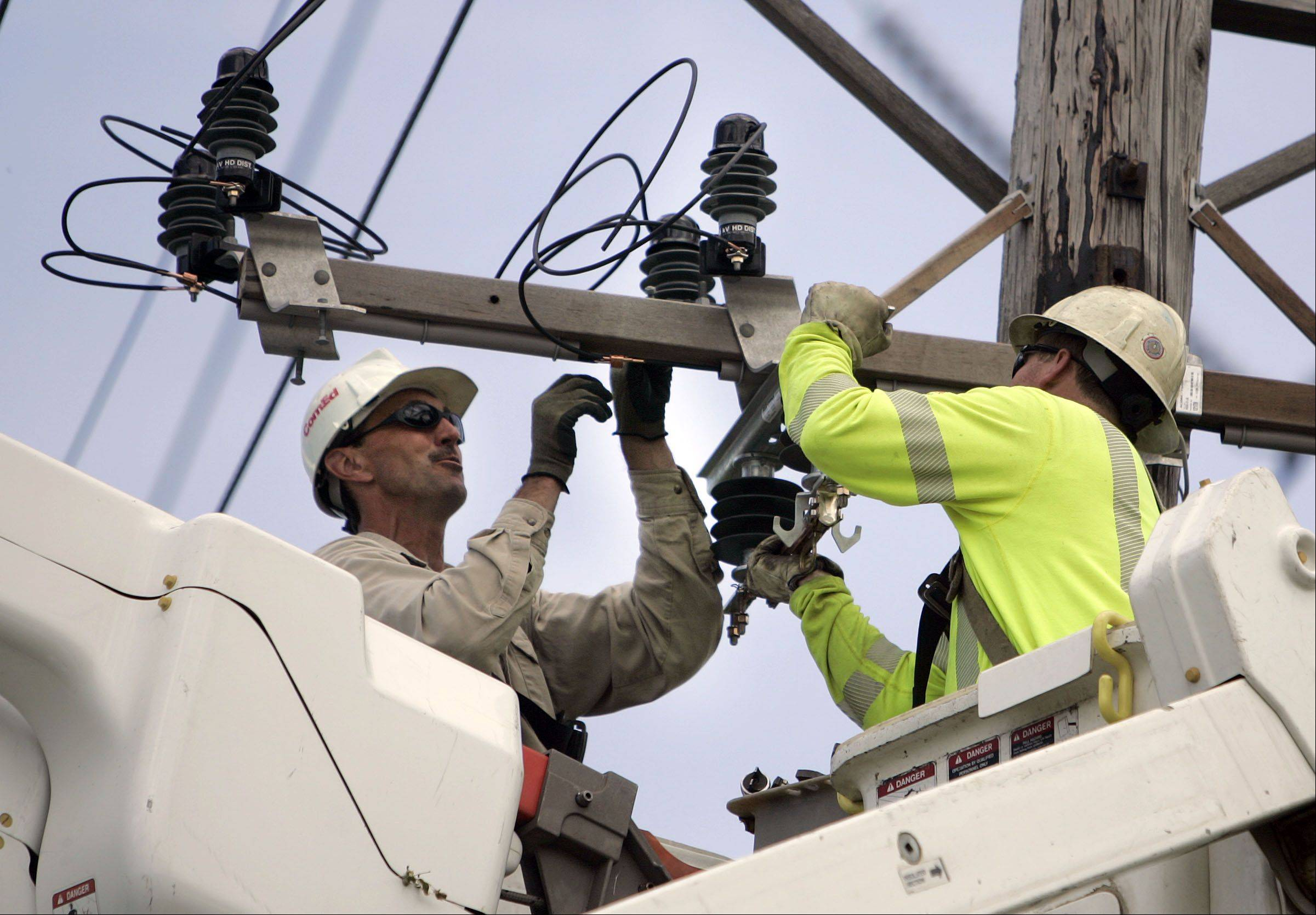 ComEd linemen John Grandfield, left, and Rob Pait work on a pole in Mundelein. Even though other companies are selling electricity to consumers, ComEd will still own and maintain the lines.