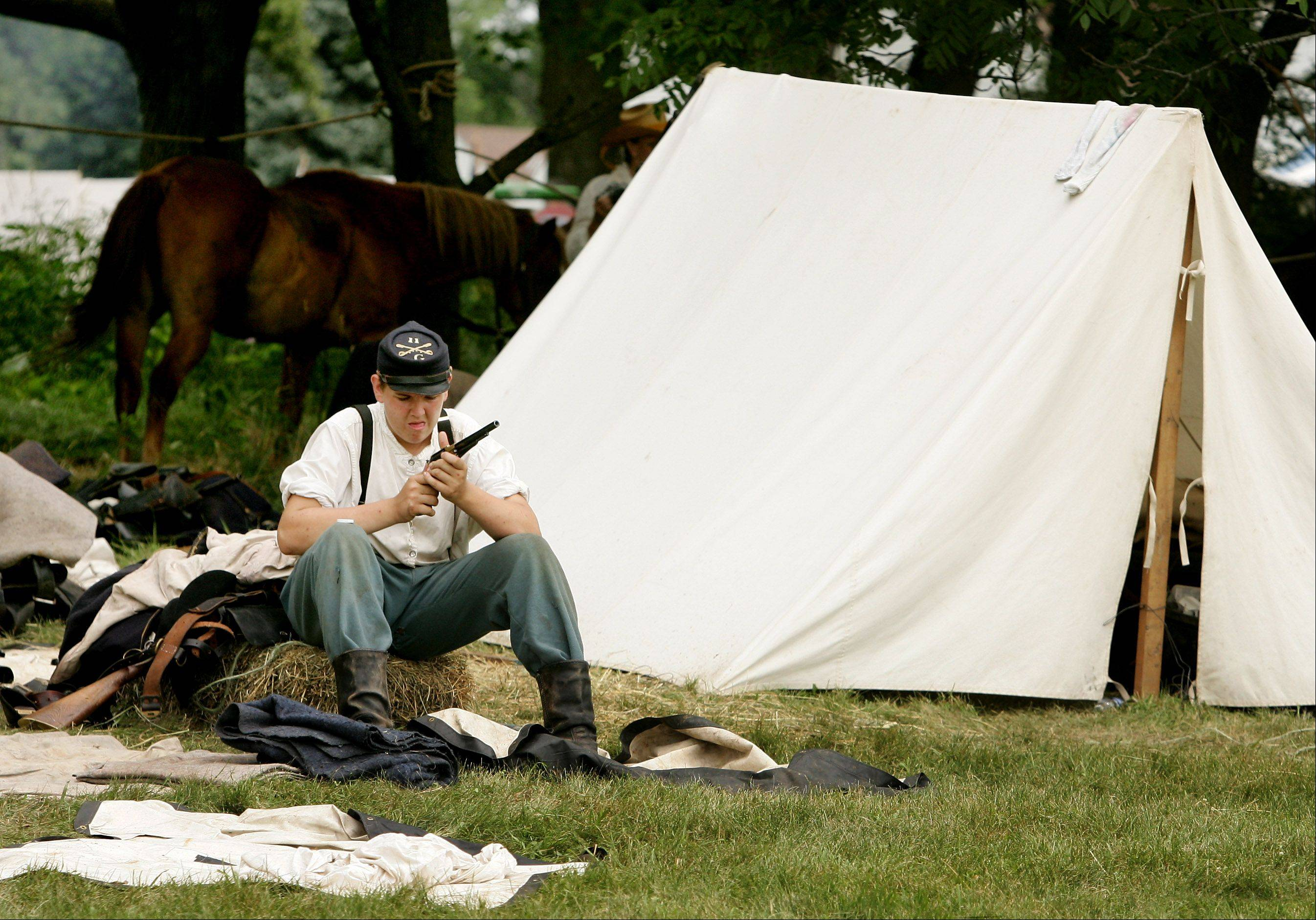 Pvt. Blake Lewis of the 11th Illinois Cavalry cleans his pistol before the afternoon battle against the Confederates during Civil War Days at Lakewood Forest Preserve near Wauconda.