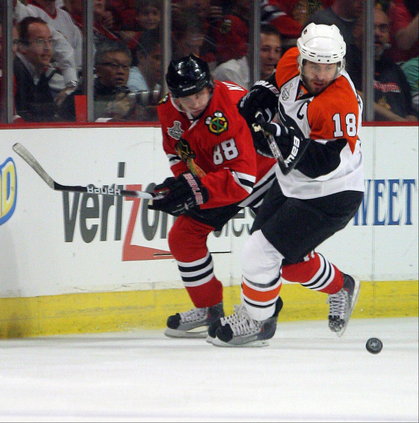 Patrick Kane and the Philadelphia Flyers' Mike Richards go for the puck during game one of the Stanley Cup finals at the United Center in Chicago Saturday.