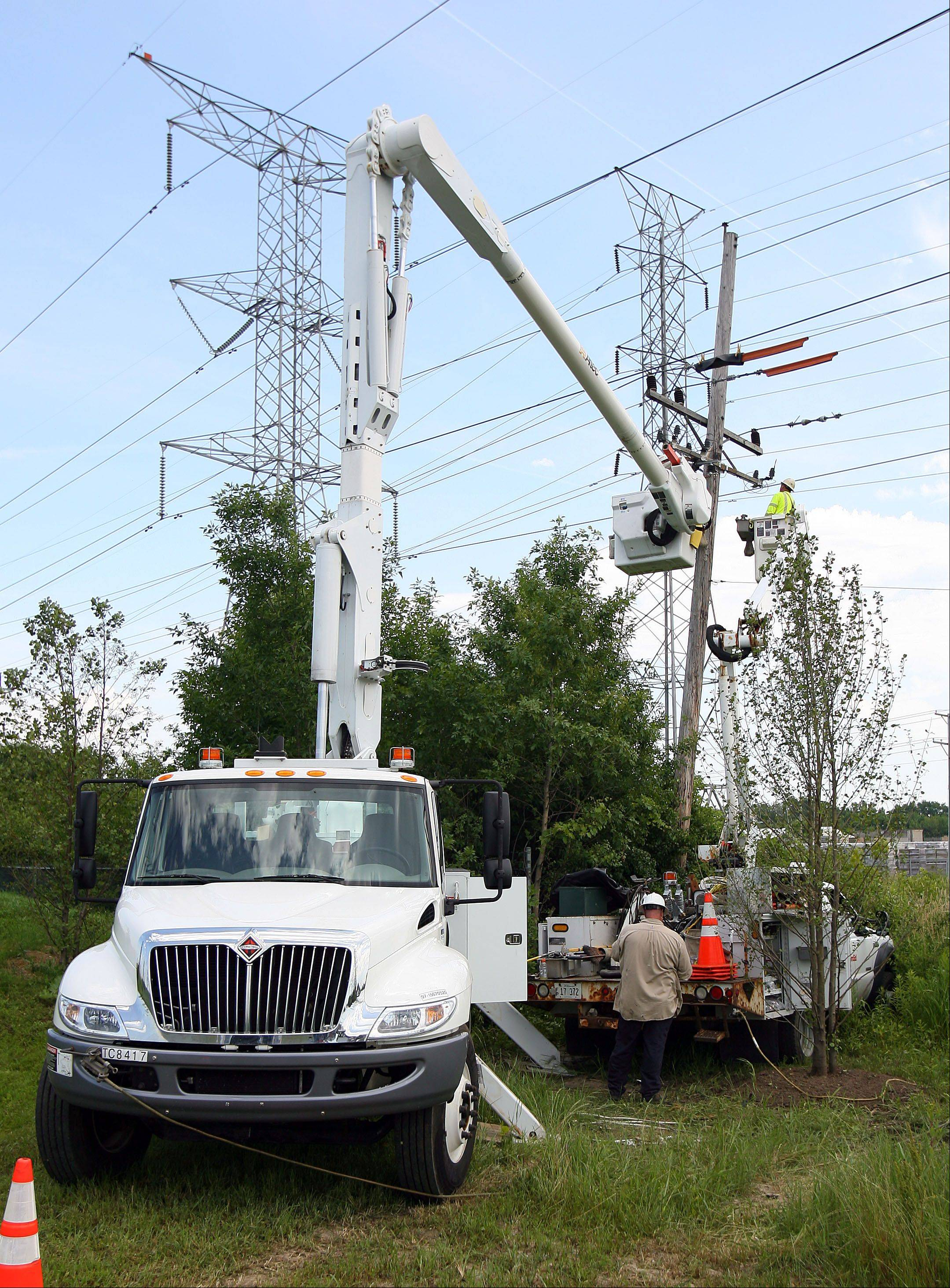 ComEd linemen work in Mundelein. Even though other companies are selling electricity to consumers, ComEd will still own and maintain the lines.