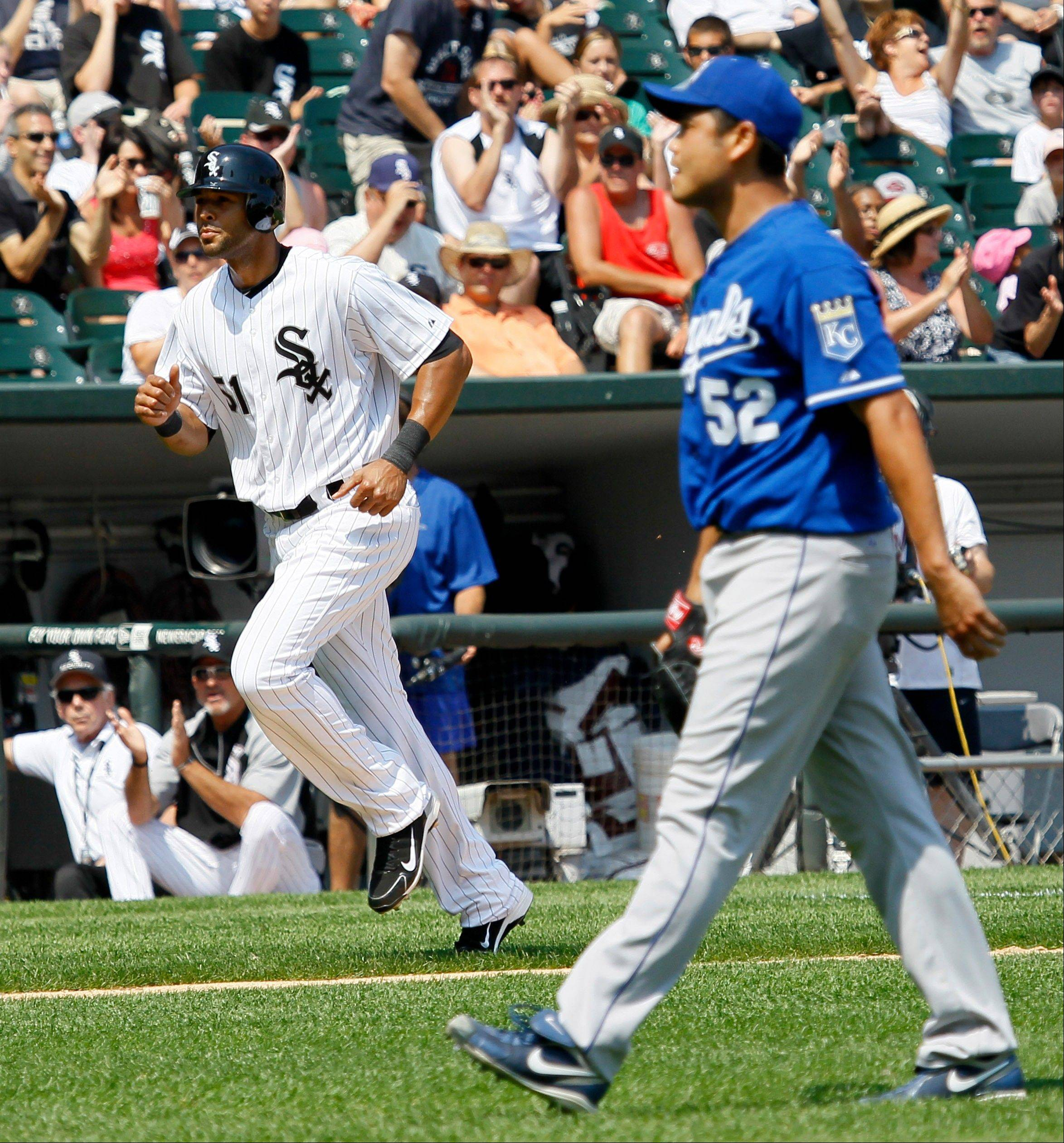 Alex Rios, left, trots home to score after Kansas City Royals starting pitcher Bruce Chen, right, walked Adam Dunn, with the bases loaded, during the sixth inning of a baseball game Wednesday, July 6, 2011 in Chicago.