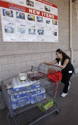 A shopper leaves Costco in Mountain View, Calif. Retailers are reporting robust sales as deep discounts on summer merchandise pulled in shoppers in June. But the concern is that the momentum may not continue heading into the back-to-school shopping season when consumers are likely to find higher prices on everything from clothing to handbags.