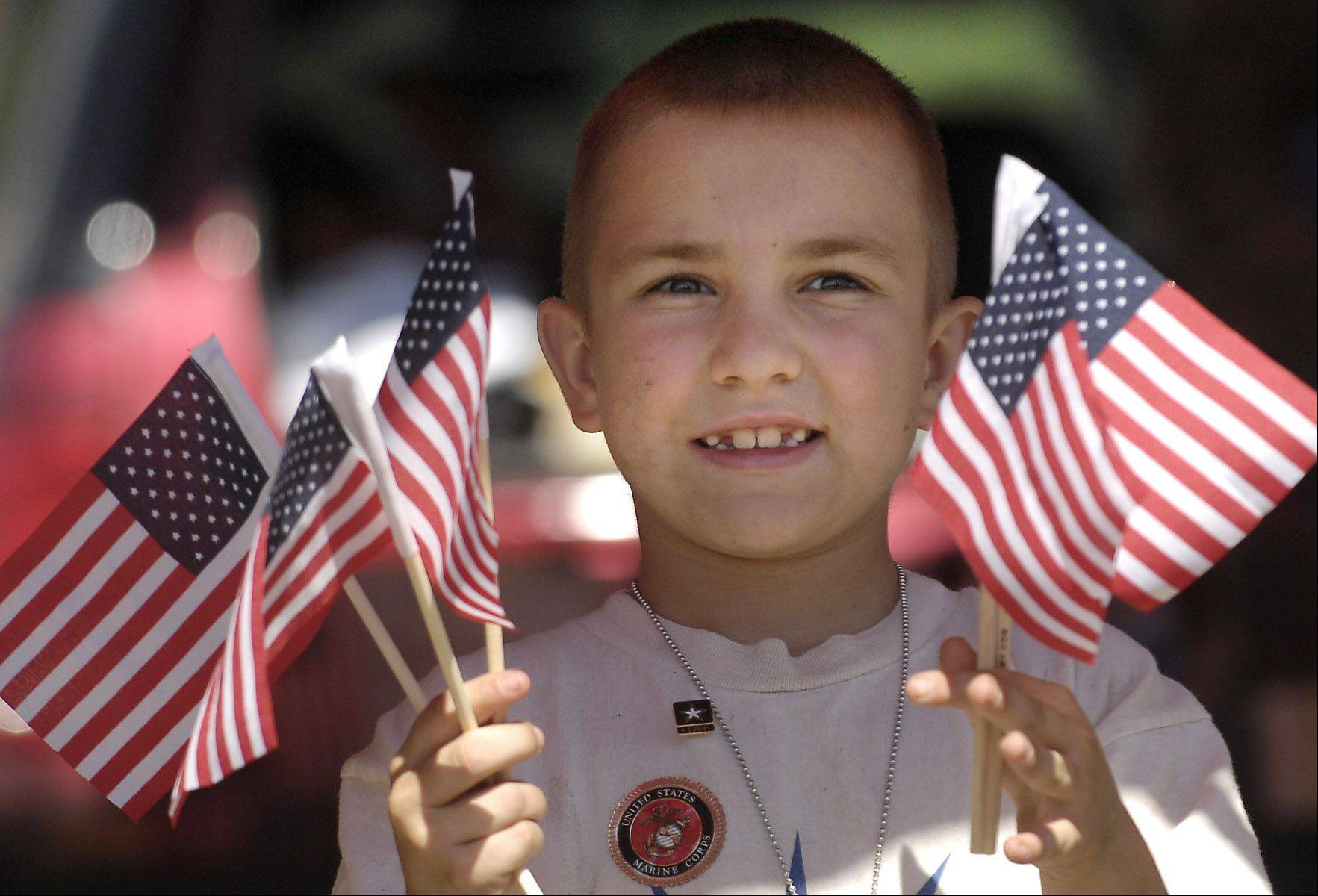 Justin Gulas, 7, of Wonder Lake hands out flags at Barrington's fourth annual Freedom Festival in 2007.