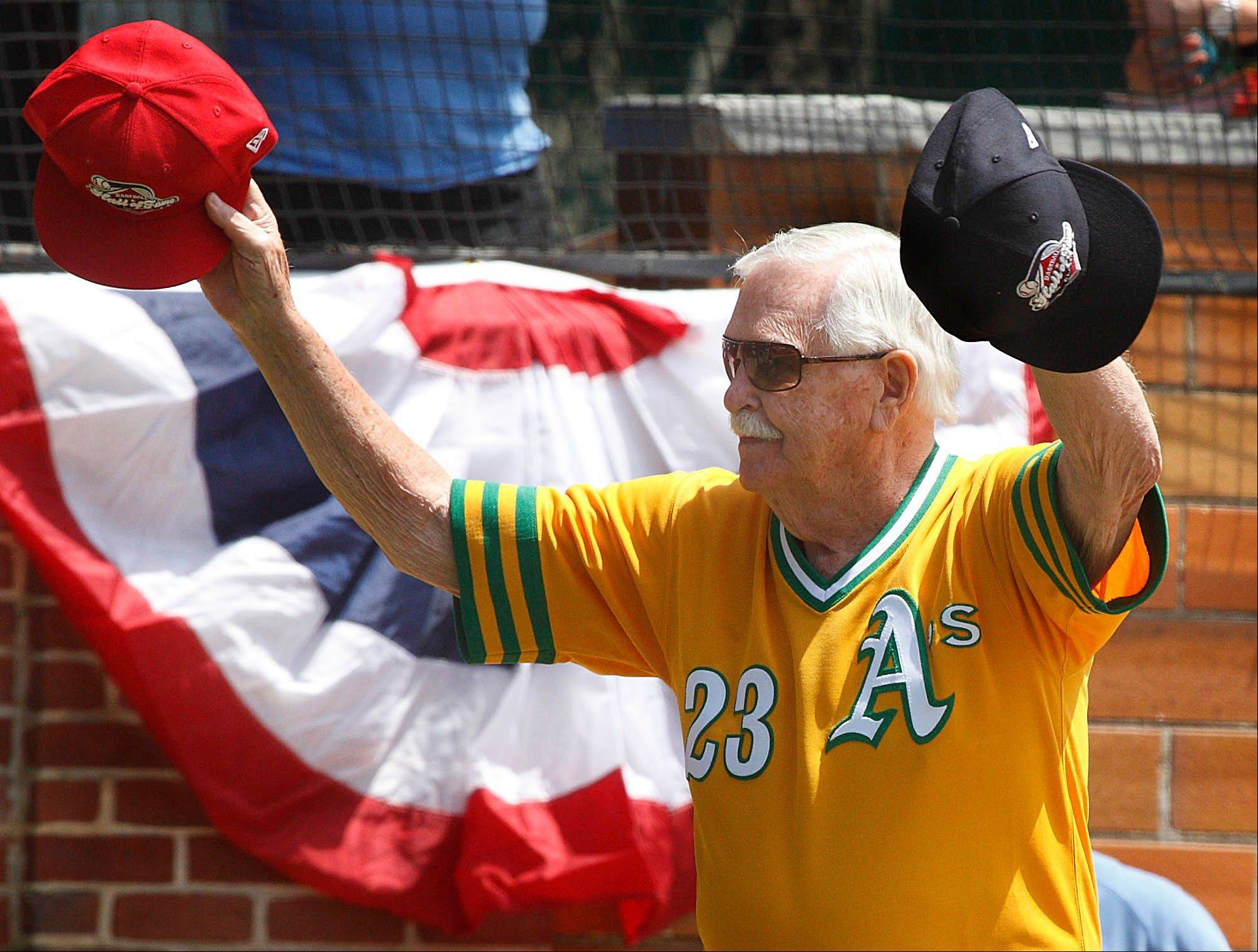 Dick Williams holds out baseball hats of the opposing teams at the National Baseball Hall of Fame Legends Game at Doubleday Field in Cooperstown, N.Y., on June 19.