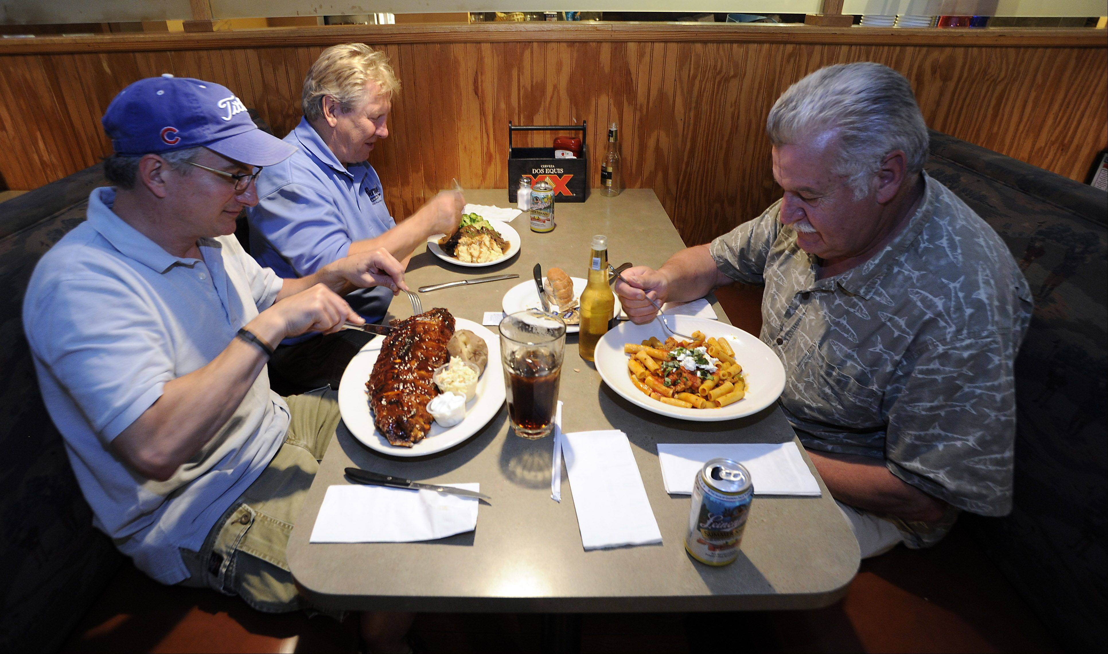 Tom Lehn of Chicago, left, Larry Dodgers of Addison and Emilio Defelipe of Chicago enjoy a meal at Club Casa Cafe in Des Plaines.
