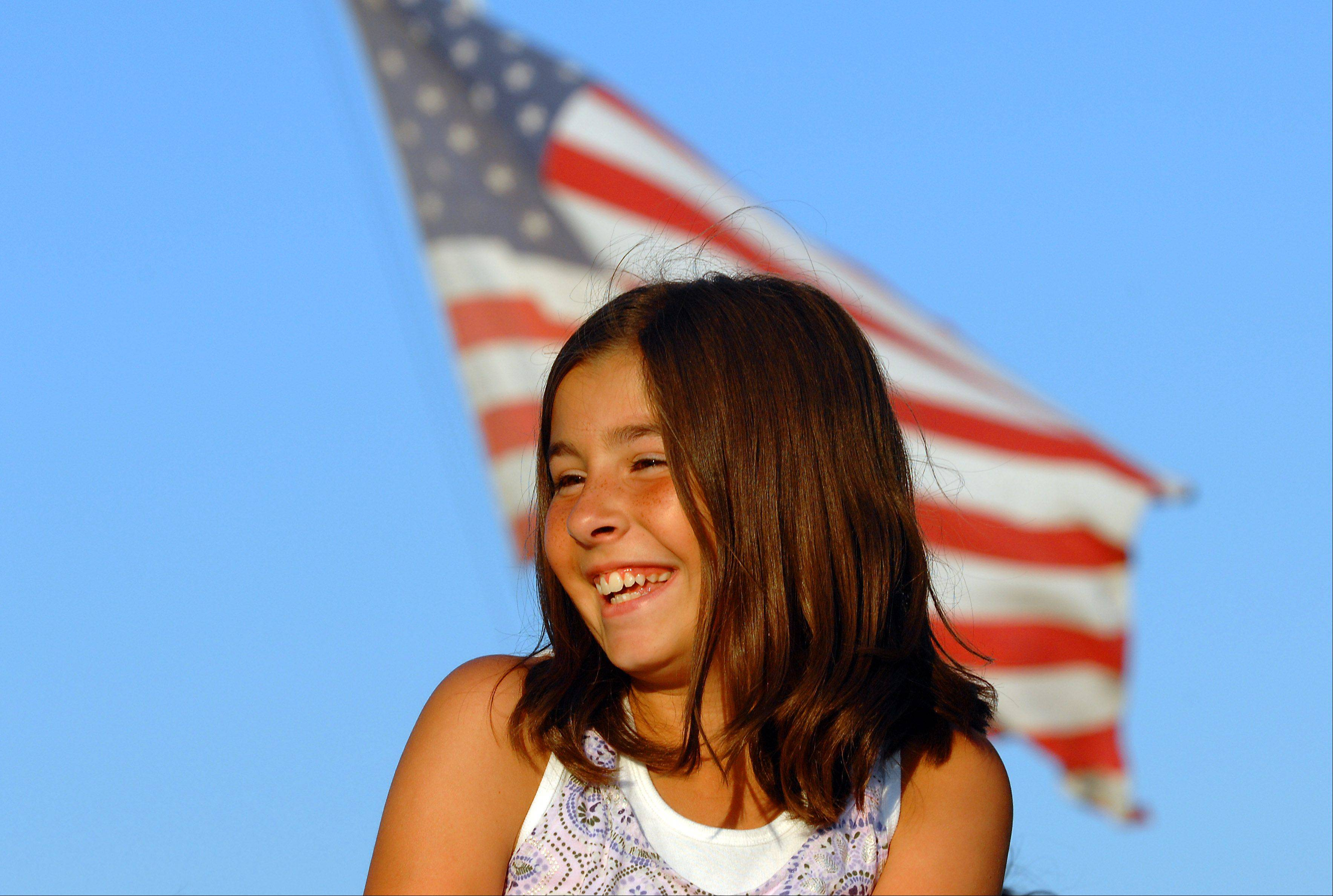 Emily Bacich, 11, of Bartlett watches a baseball game Thursday across from where Bartlett firefighters hoisted a 75-pound American flag atop a fire truck's tower to honor Sept. 11 emergency workers.