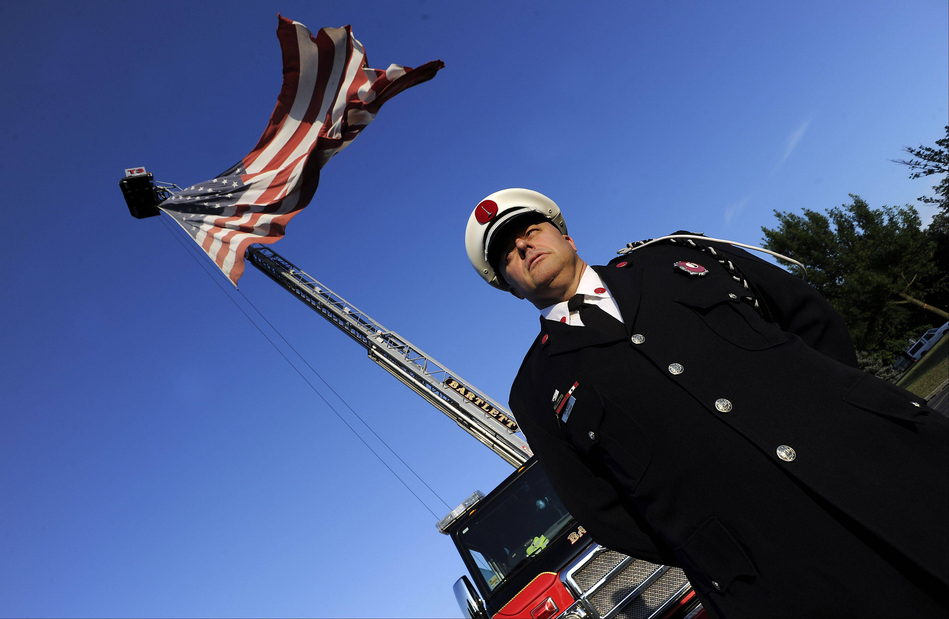 Lieutenant Dave Bosse of the Bartlett Fire Department stands at attention Thursady as a giant American flag waves above a fire truck in Bartlett.