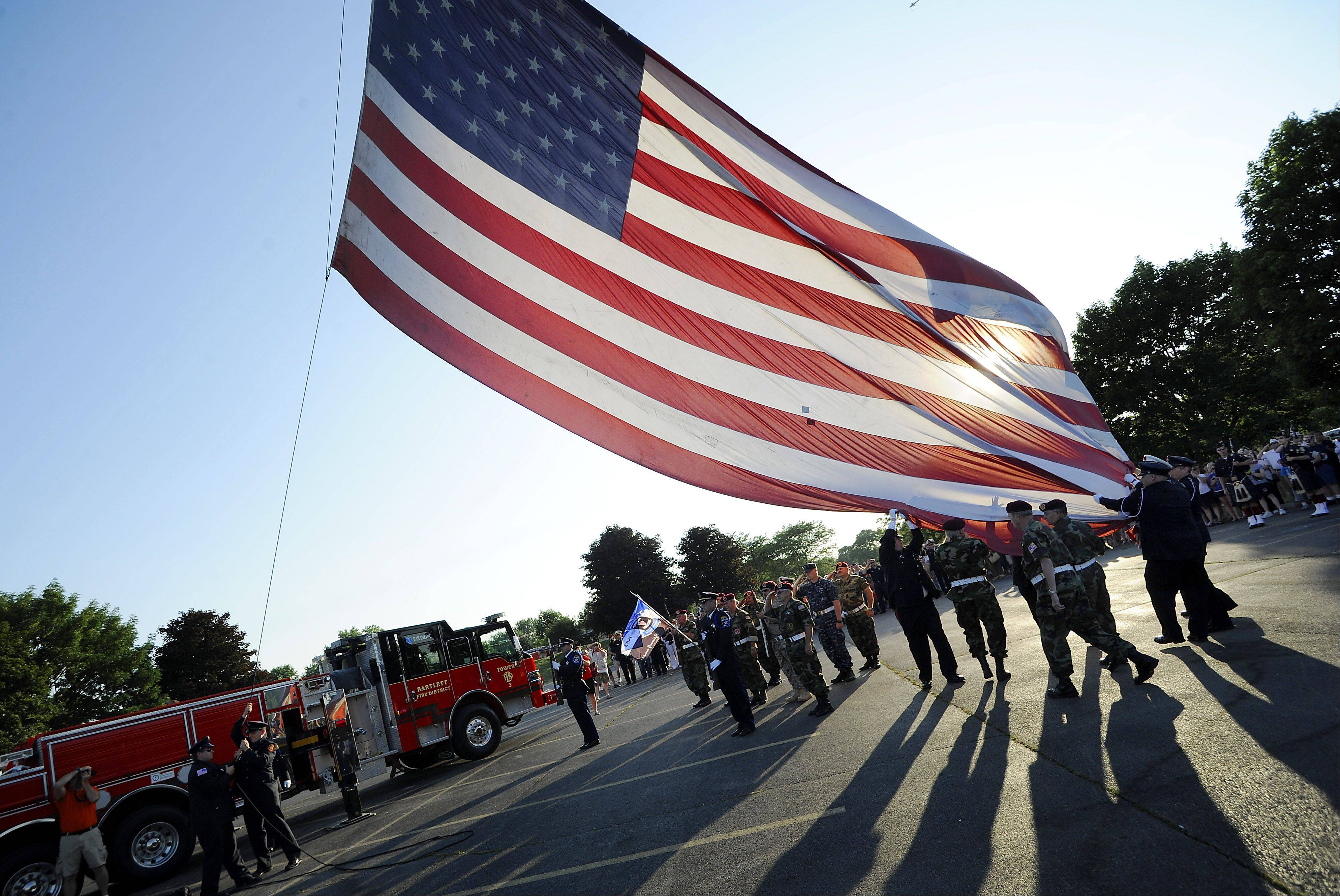 Members of the Bartlett Fire Department hoist the 75lb flag up their fire truck's tower getting ready to display old glory in all her splendor honoring September 11th emergency workers.