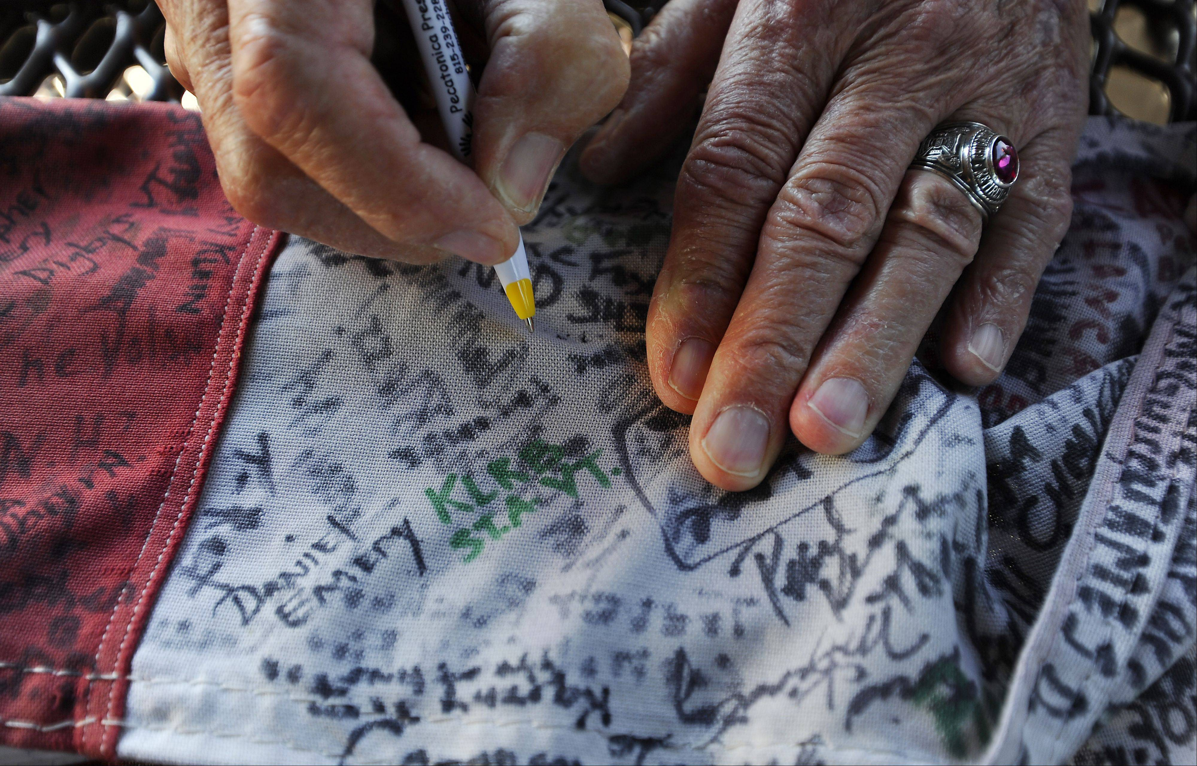 People write messages on sections of remnant of the flag.