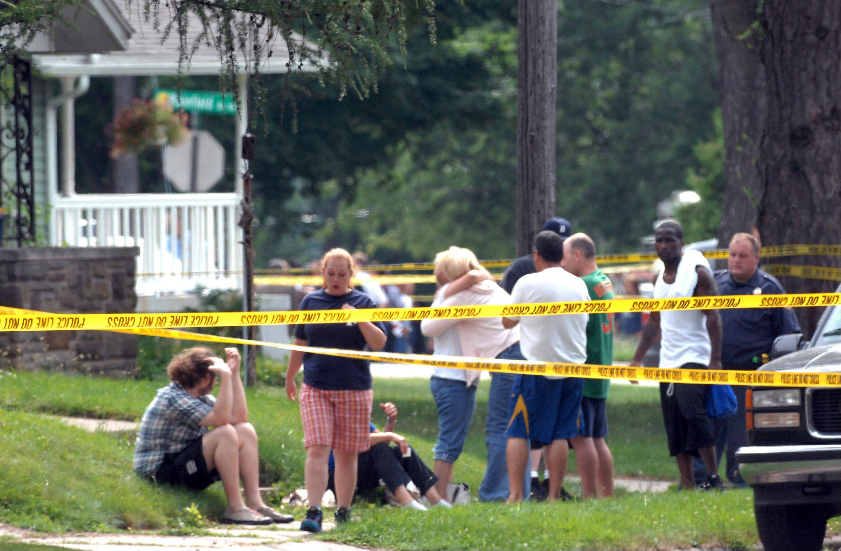 People react near the scene in Grand Rapids, Mich., where three bodies were found Thursday, July 7, 2011. Police say seven people have been fatally shot at two locations in the western Michigan city and the victims include a child.