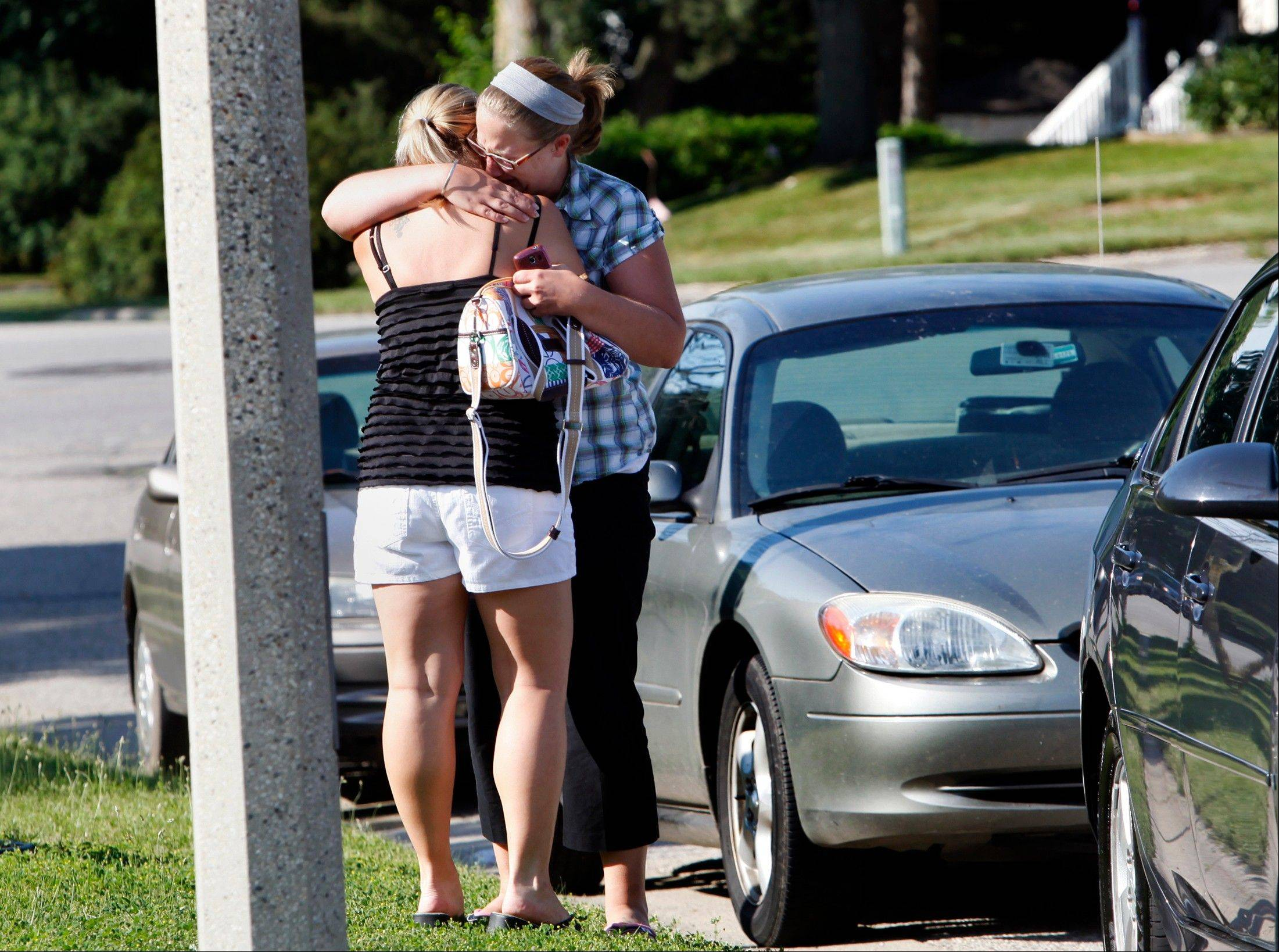 Tricia Jimenez, 27, of Grand Rapids, left, and a close friend grieve after finding out their close friends' parents were murdered in their home on Brynell Avenue in Grand Rapids, Mich. Thursday, July 7, 2011. Four victims were found in the basement, and another three were found another home across town.