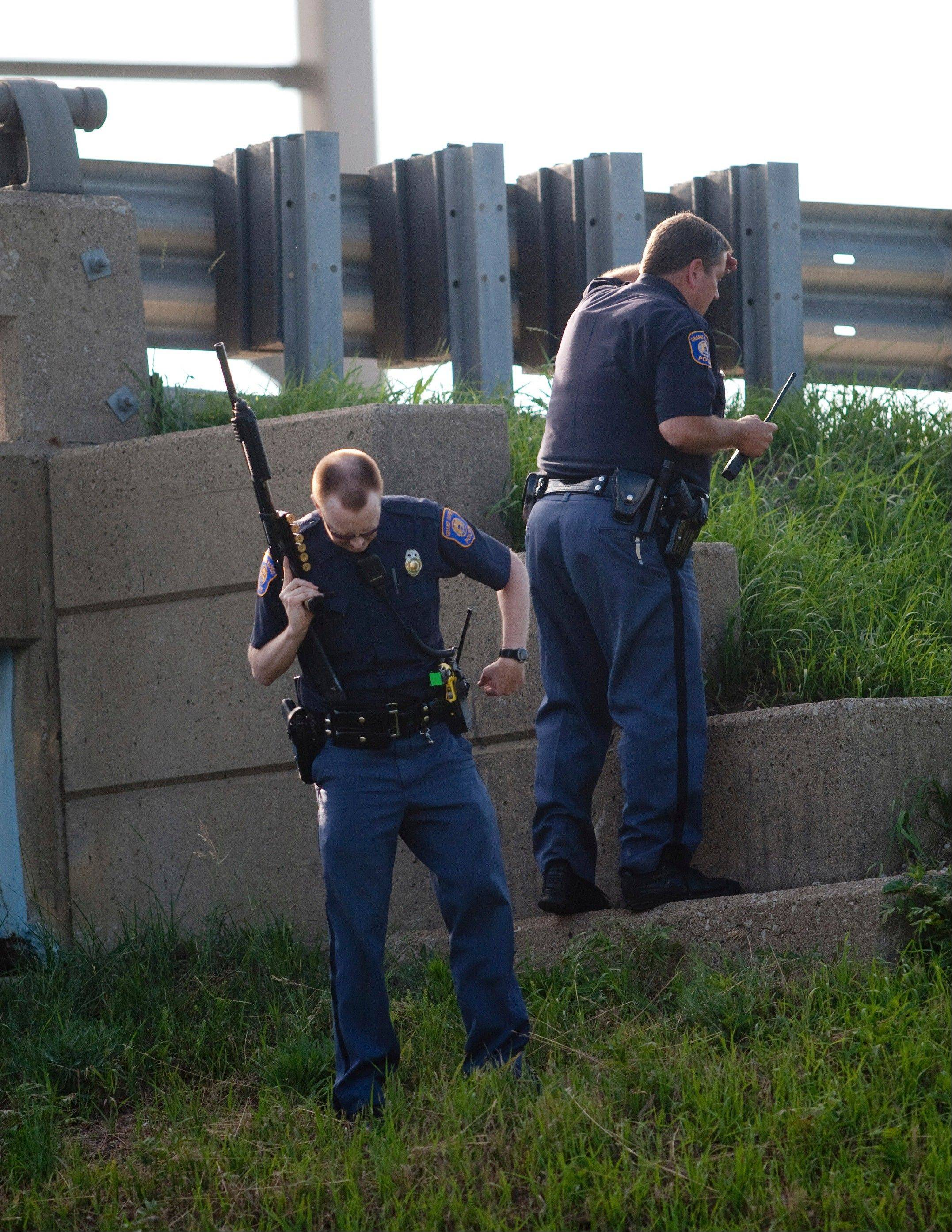 Police officers check the embankment alongside Interstate 131 northbound in Grand Rapids, Mich., after a high-speed car chase in pursuit of a shooting spree suspect, Thursday, July 7, 2011.