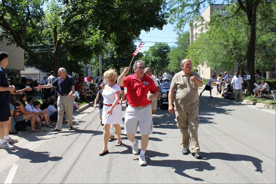 Gov. Pat Quinn, left, walks alongside Des Plaines city officials during the July Fourth parade shaking hands of spectators. Des Plaines Mayor Marty Moylan leads the group waving a flag with 2nd Ward Alderman John Robinson to his right, and 1st Ward Alderman Patricia Haugeberg and 4th Ward Alderman Dick Sayad walking behind him.