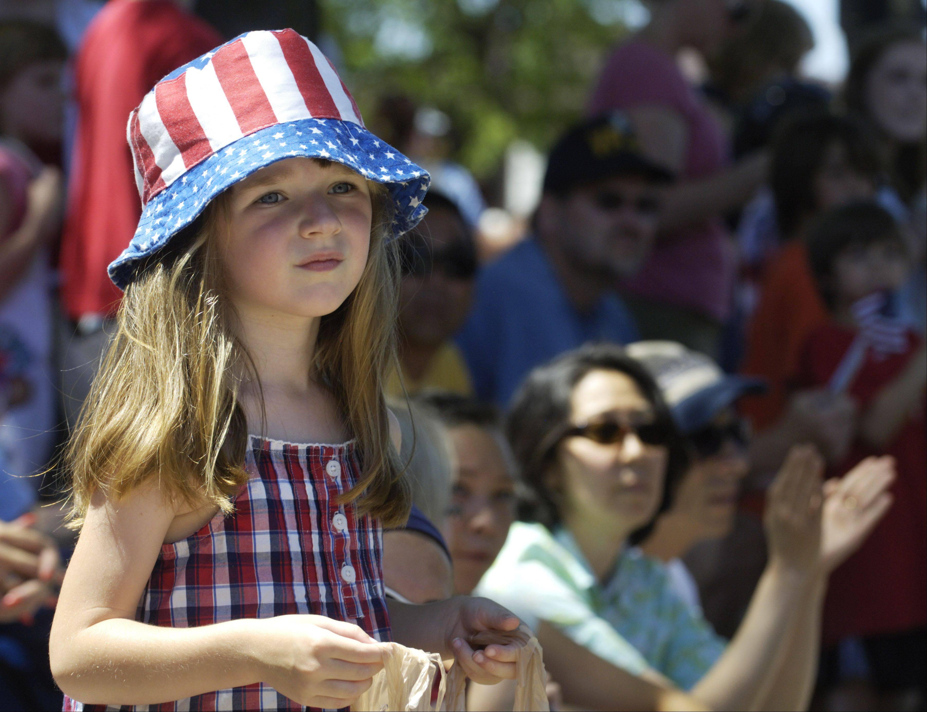 Amanda Mattson, 5, of Mount Prospect holds her candy bag while watching the Mount Prospect Fourth of July parade Monday.