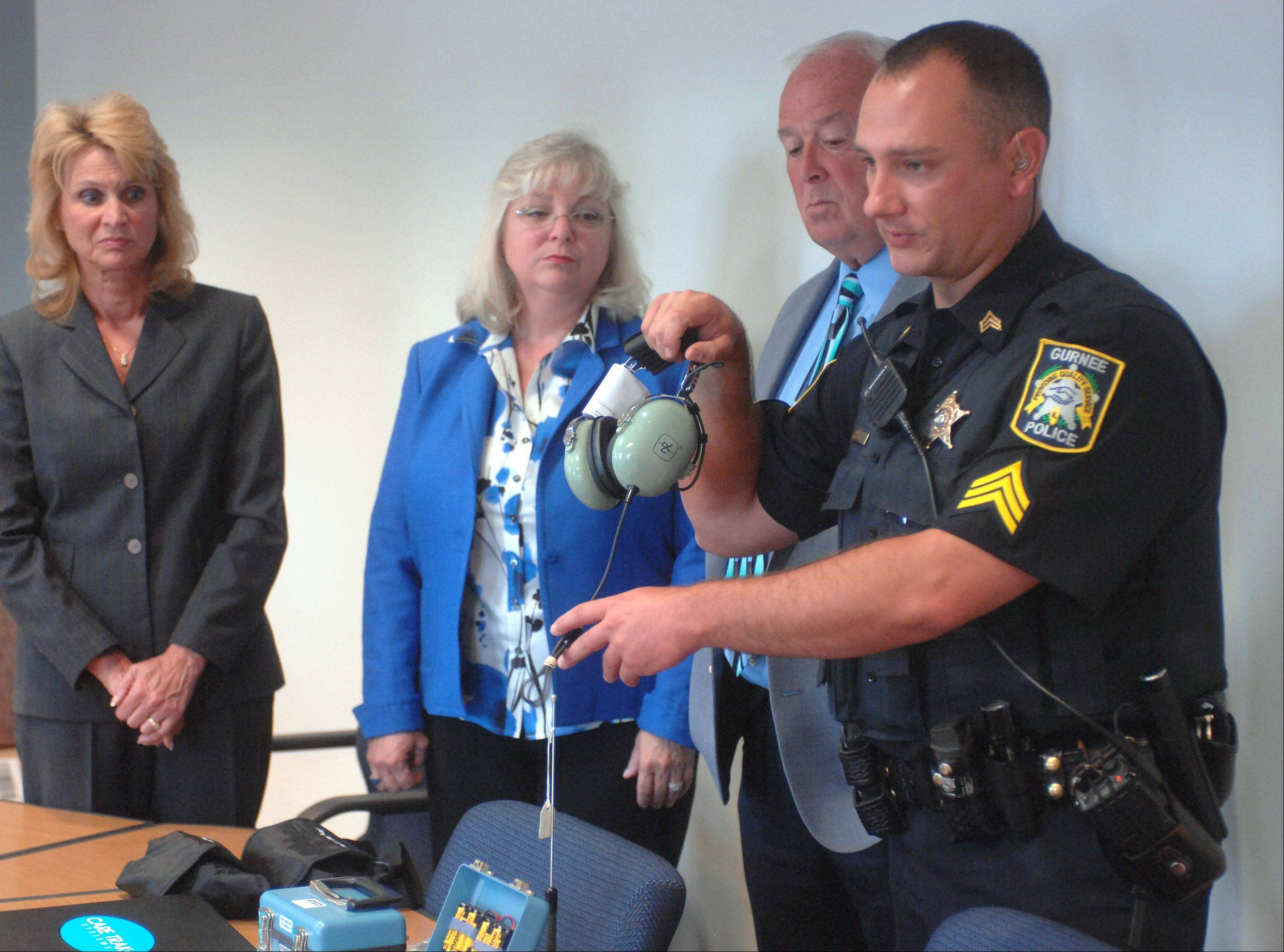 Gurnee police Sgt. Brian Smith, right, explains the Care Trak equipment Thursday morning in Gurnee during a news conference. From left, Mayor Kristina Kovarik, Warren Township supervisor Sue Simpson and Gurnee police chief Bob Jones also participated in the announcement.