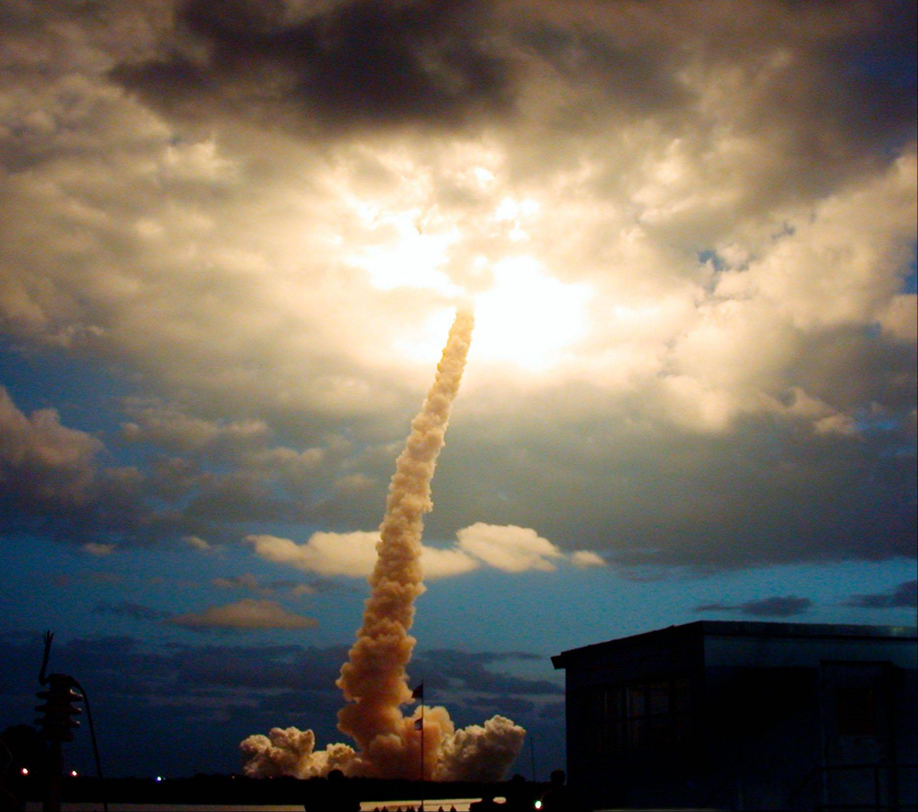 In this Friday, March 1, 2002 file picture, the space shuttle Columbia illuminates a cloud during its morning liftoff at the Kennedy Space Center in Cape Canaveral, Fla.