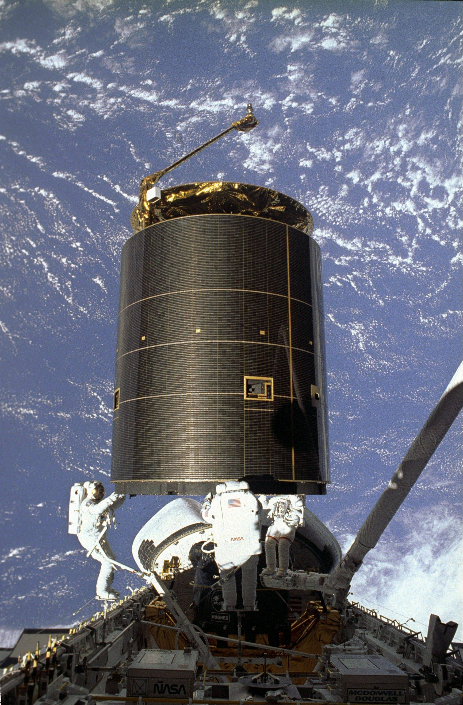 In this May 13, 1992 picture made available by NASA, astronauts Richard Hieb, Thomas Akers and Pierre Thuot grab the Intelsat VI satellite from the ledges of the payload bay of the space shuttle Endeavour in the first three-man spacewalk. The satellite had been stuck at a uselessly low orbit for more than two years.