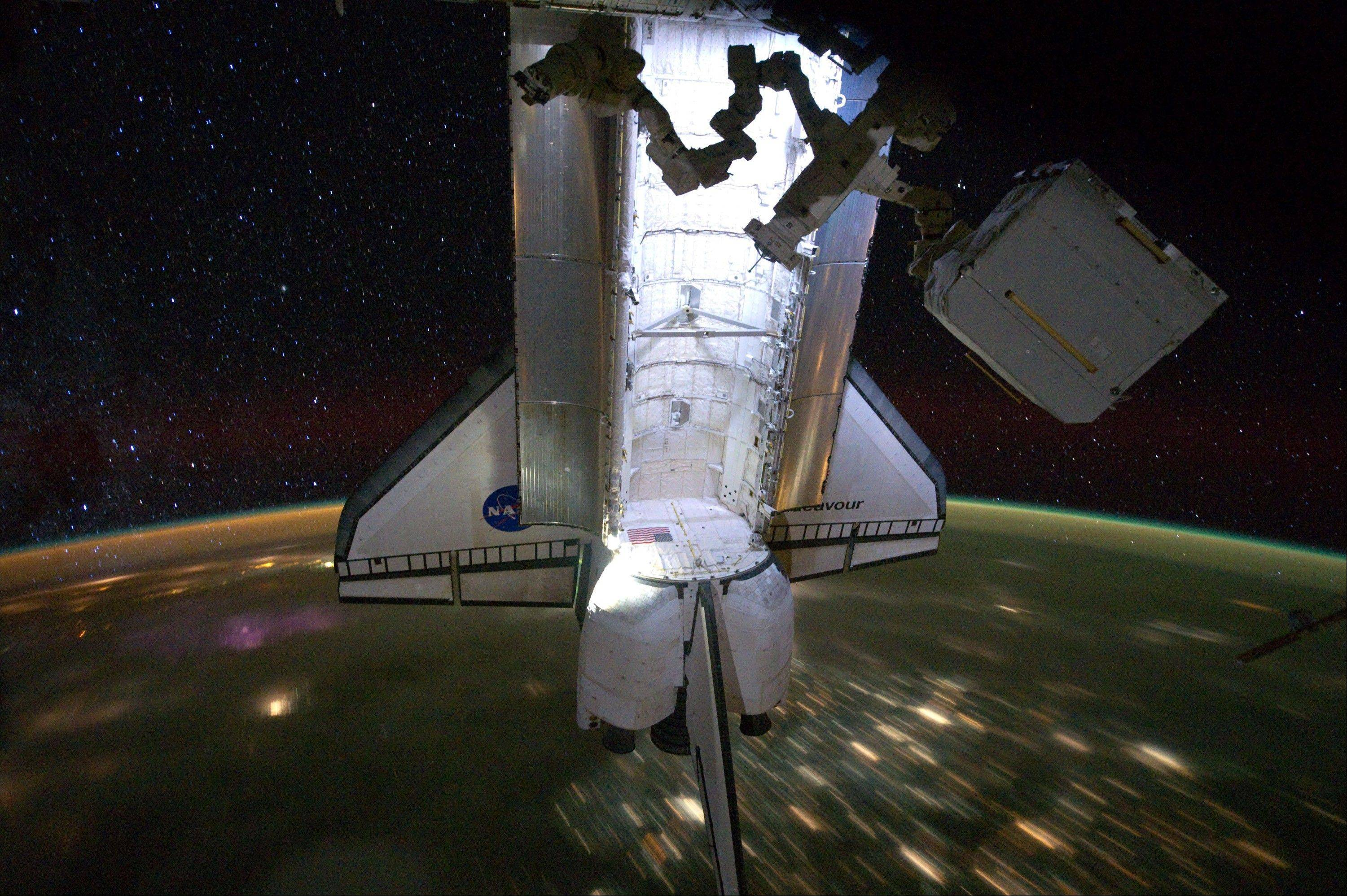 This Saturday, May 28, 2011 photo provided by NASA shows the Endeavour with a nighttime view of the Earth and a starry sky, while docked at the International Space Station during the Endeavour's final mission.