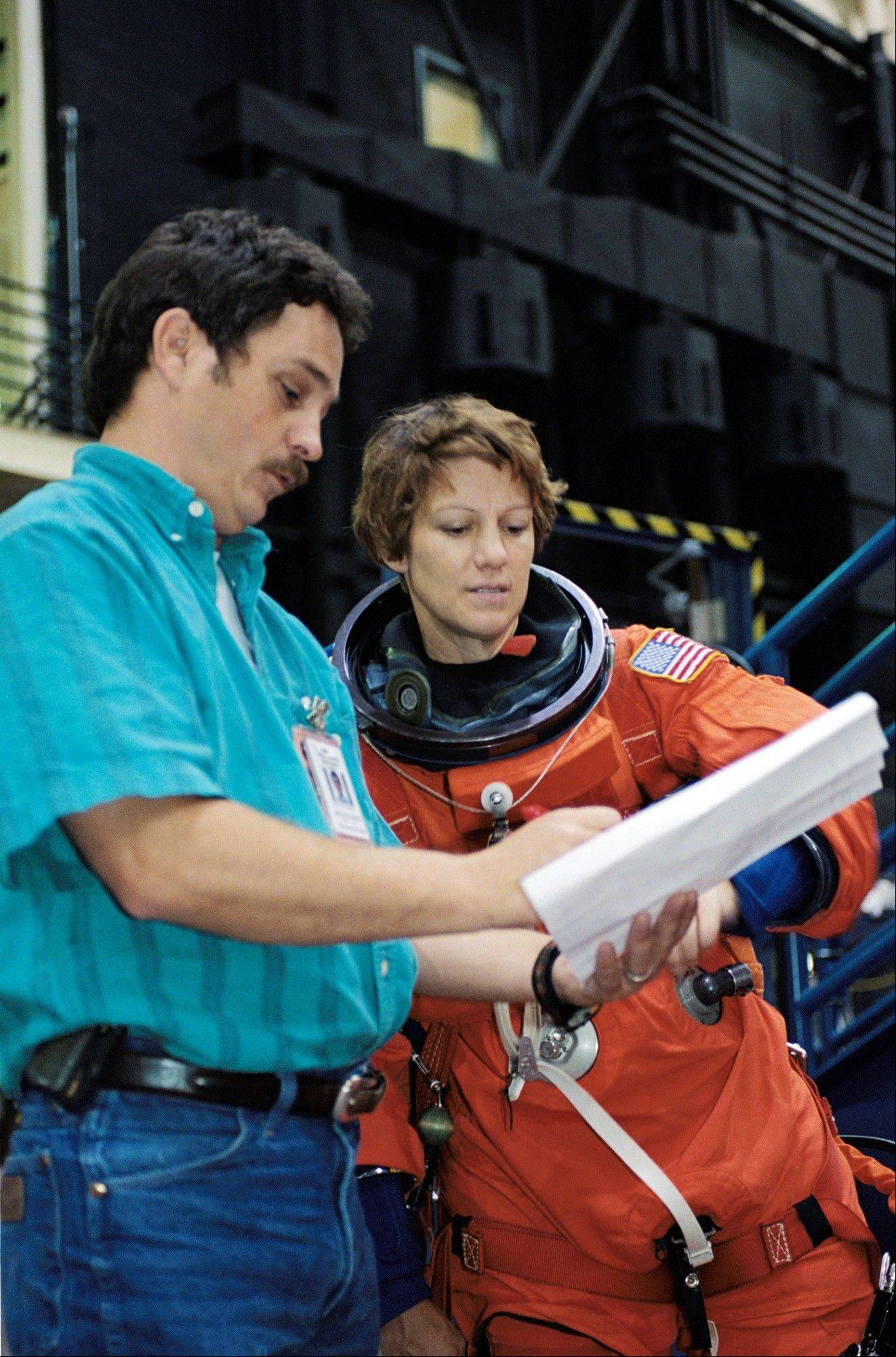 In this Sept. 12, 2002 file picture, astronaut Eileen Collins, commander for the space shuttle Discovery mission scheduled for May 2005 launch, is briefed by crew trainer Ken Trujillo during a training session in the Space Vehicle Mockup Facility at Johnson Space Center in Houston.