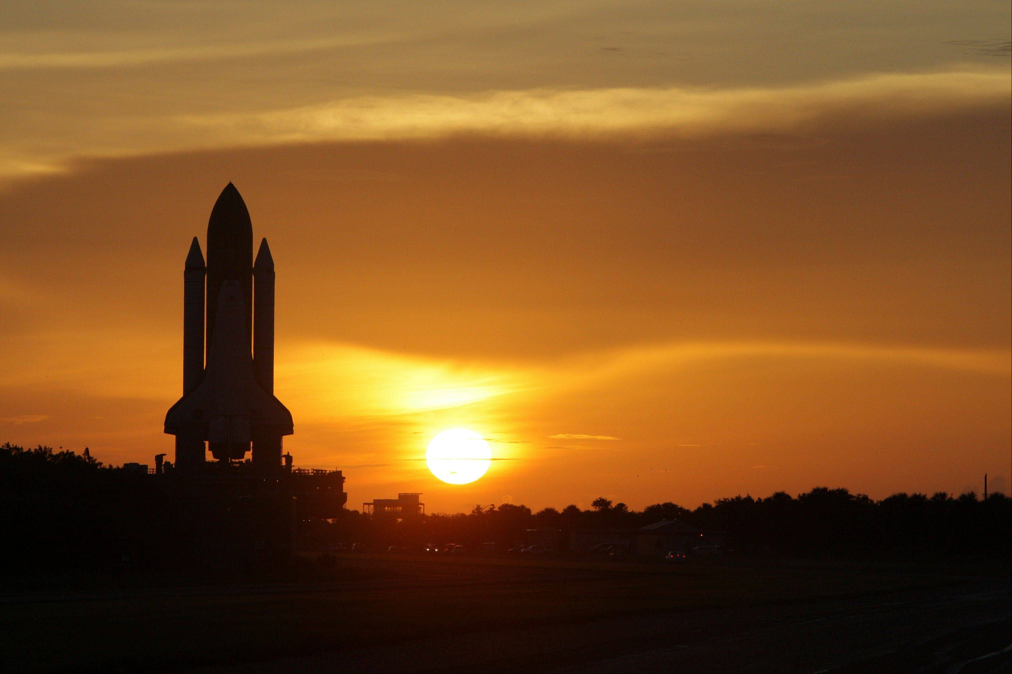 In this Tuesday, Aug. 4, 2009 file photo, Space shuttle Discovery moves along it's path at sunrise to pad 39A at the Kennedy Space Center in Cape Canaveral, Fla. The space shuttle was sold to America as cheap, safe and reliable. It was none of those. It cost tens of billions of dollars, ended the lives of 14 astronauts and managed to make fewer half the flights promised. Yet despite all that, there were monumental achievements that in the beginning were unforeseen: major scientific advances, stunning photos of the cosmos, a high-flying vehicle of diplomacy that helped bring Cold War enemies closer, and something to brag about.