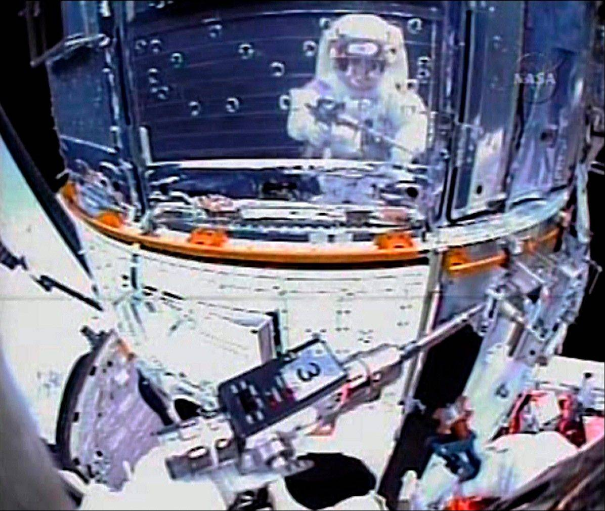 In this Monday, May 18, 2009 image made from video provided by NASA, astronaut John Grunsfeld is reflected on the surface of the Hubble Space Telescope as he works to upgrade the orbiting observatory during a spacewalk on the fifth and final repair mission for the then 19-year-old telescope.