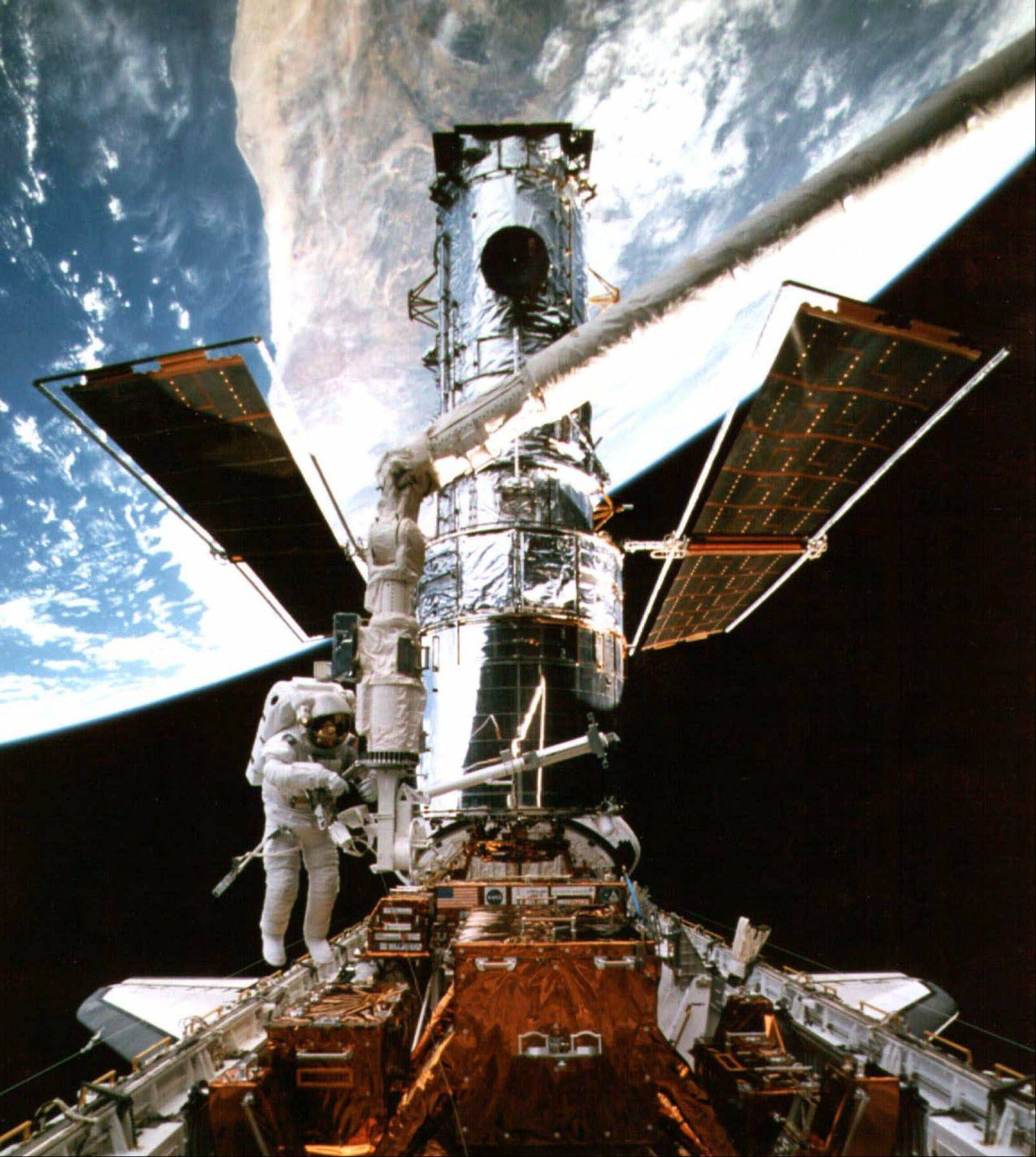 In this Feb. 15, 1997 picture provided by NASA, astronaut Steven Smith works at the end of the space shuttle's remote manipulator system as he performs maintenance on the Hubble Space Telescope during a spacewalk. In the background is a portion of Australia along the Earth's curve.