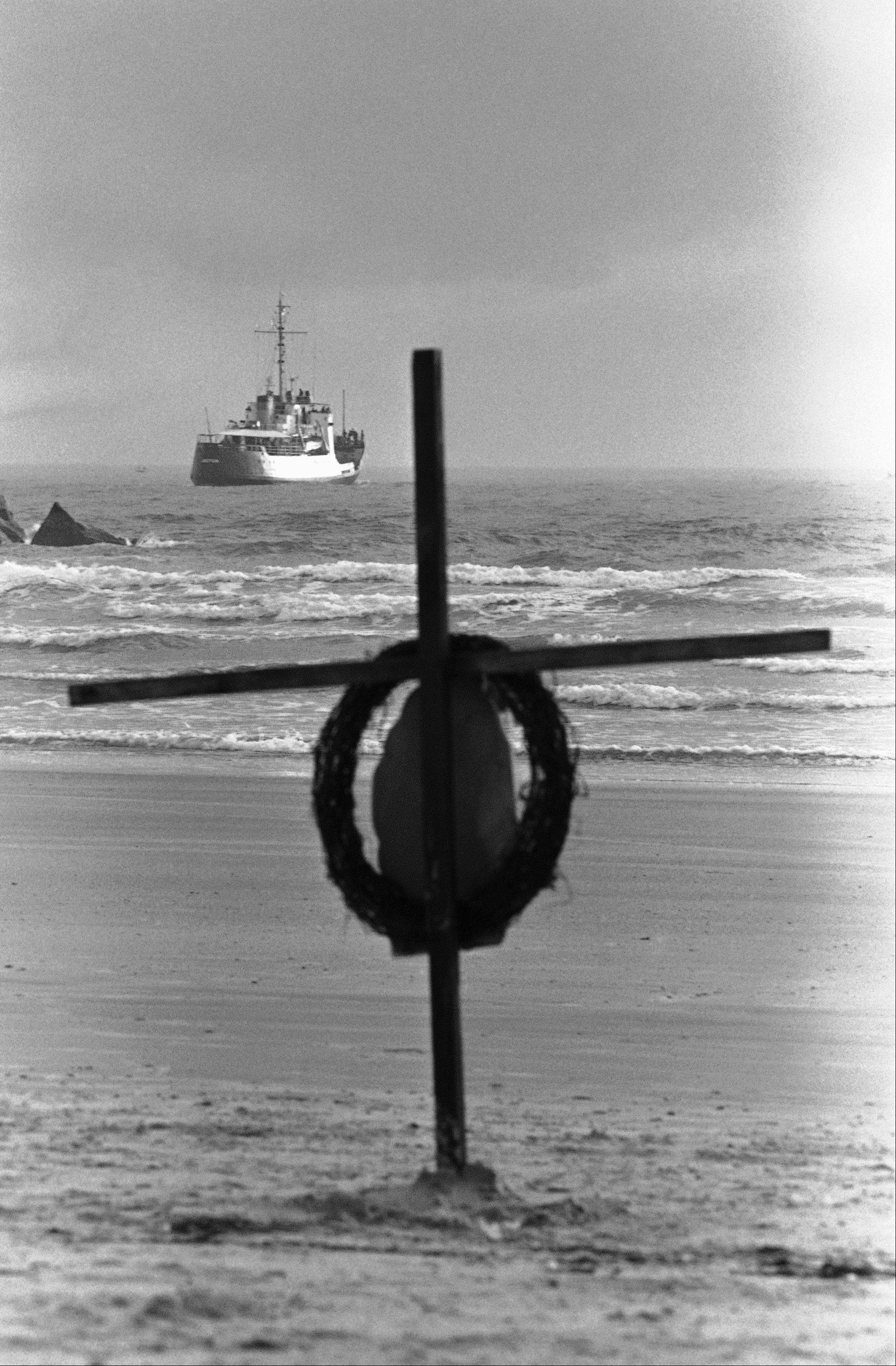 In this Saturday, Feb. 1, 1986 file picture, a cross and wreath with a picture of the space shuttle Challenger stand on the shore as a Coast Guard cutter heads out to sea searching for debris from the shuttle in Cape Canaveral, Fla.