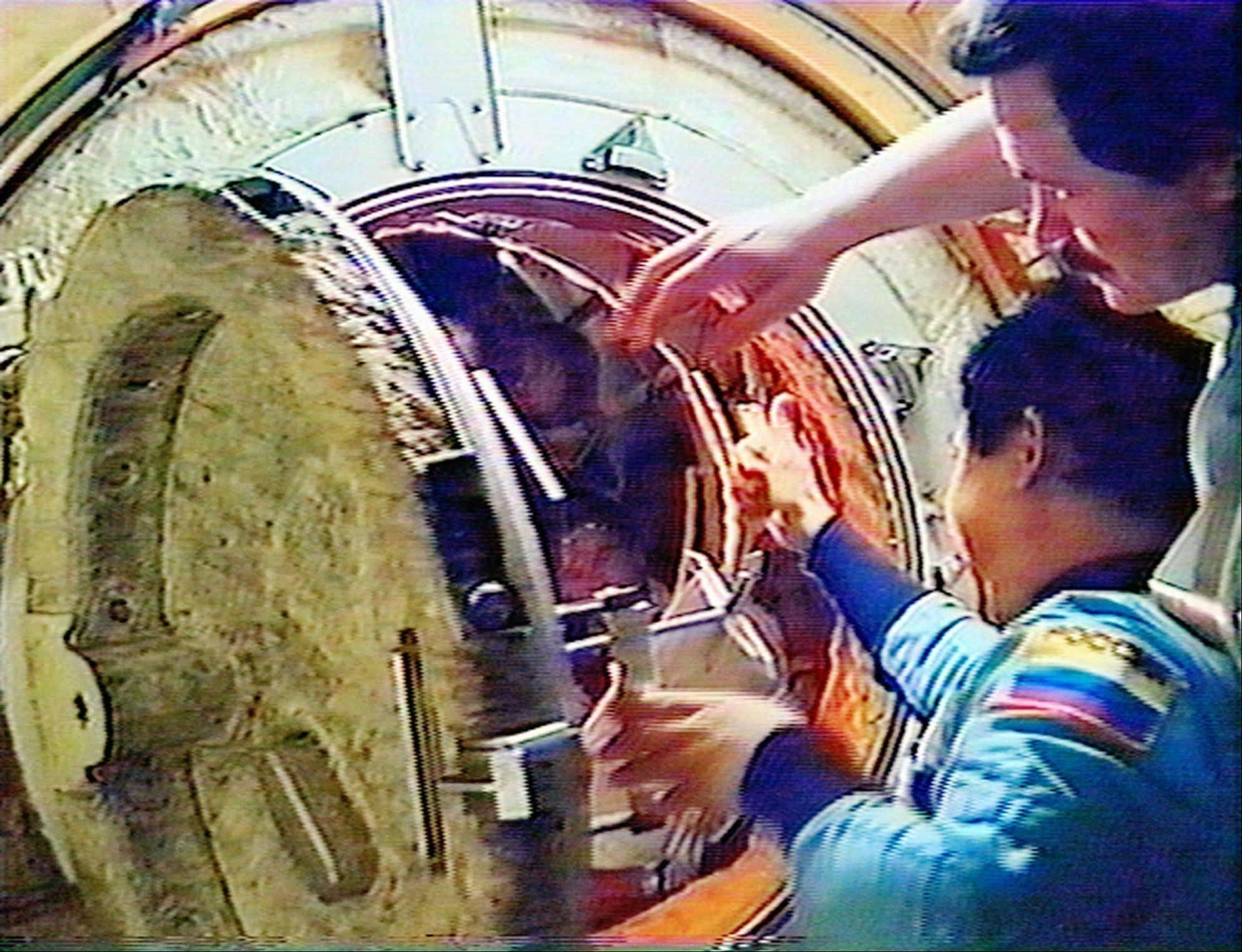 In this Monday, June 8, 1998 image made from video provided by NASA, Russian space station Mir cosmonauts Nikolai Budarin, top right, and Talgat Musabayev say goodbye to the crew of the space shuttle Discovery as they close the hatch linking the two spacecraft before undocking. Discovery was the ninth and last shuttle to dock with Mir.