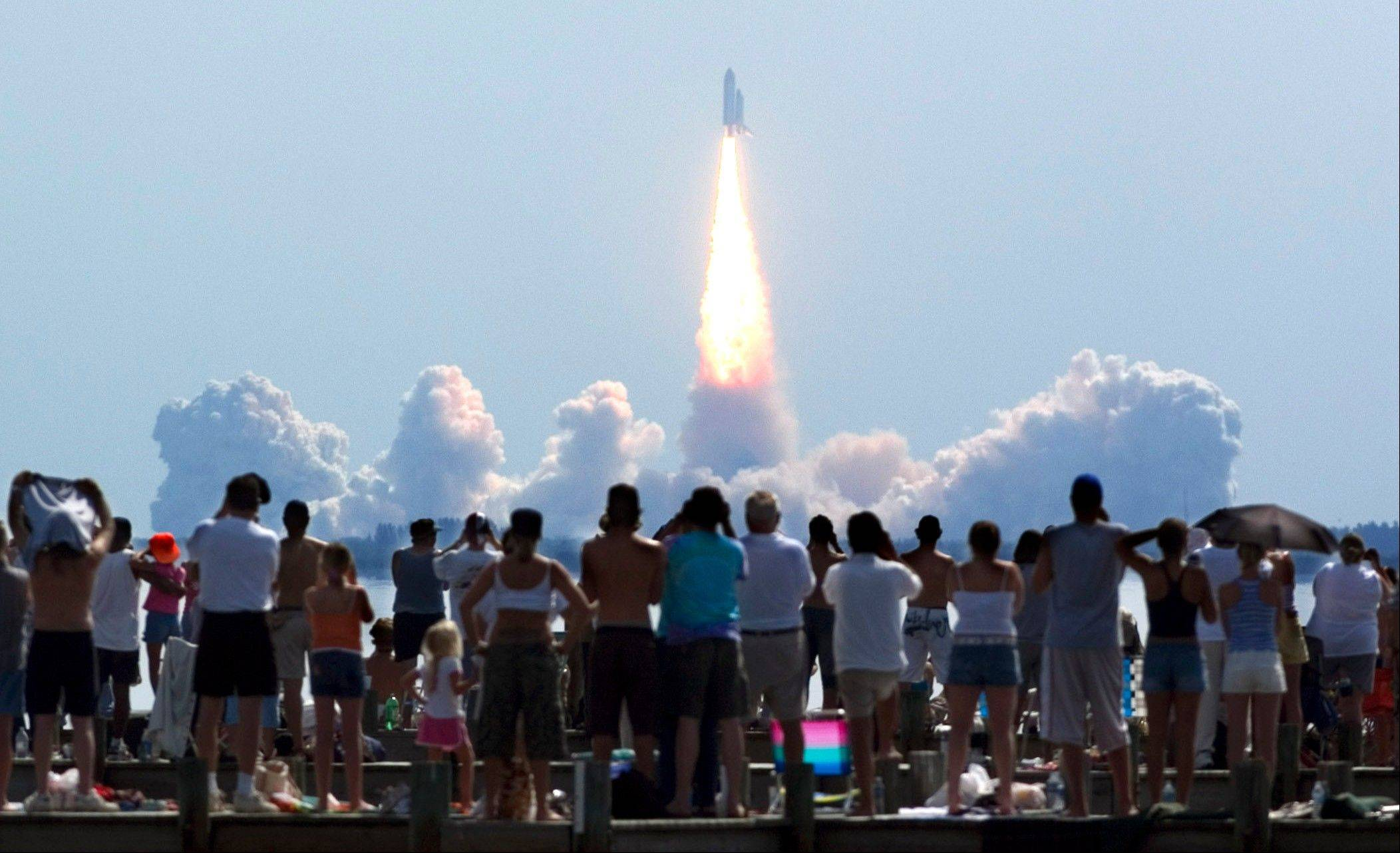In this Tuesday, July 26, 2005 file picture, crowds watch as the space shuttle Discovery lifts off from Kennedy Space Center in Cape Canaveral, Fla. The seven astronauts launched into orbit on America's first manned space mission since the 2003 Columbia disaster.