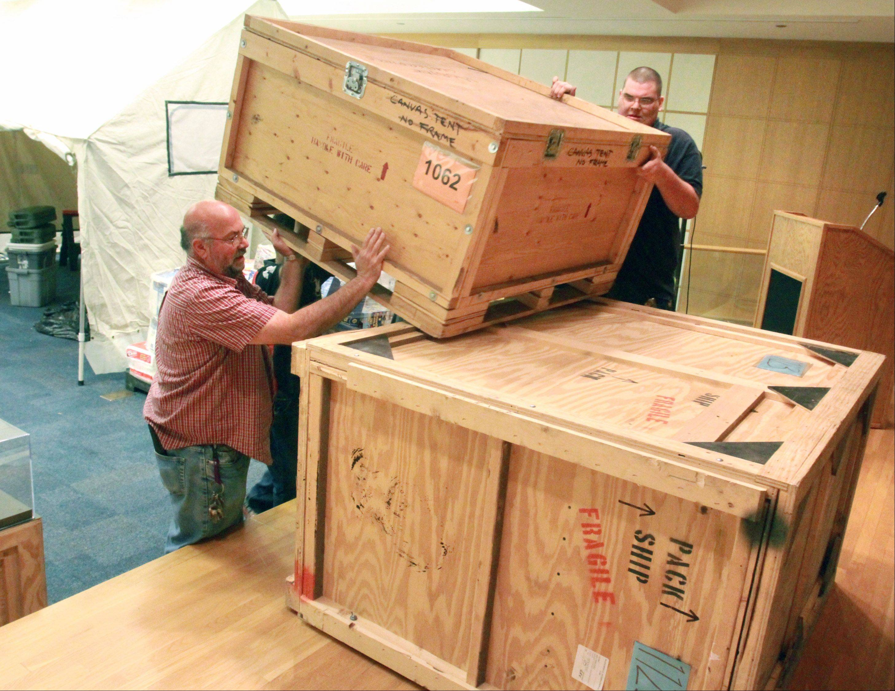 Tom Scuderi, left, and Bill Benne with the Arlington Heights Library stack crates on the stage area of the exhibit.