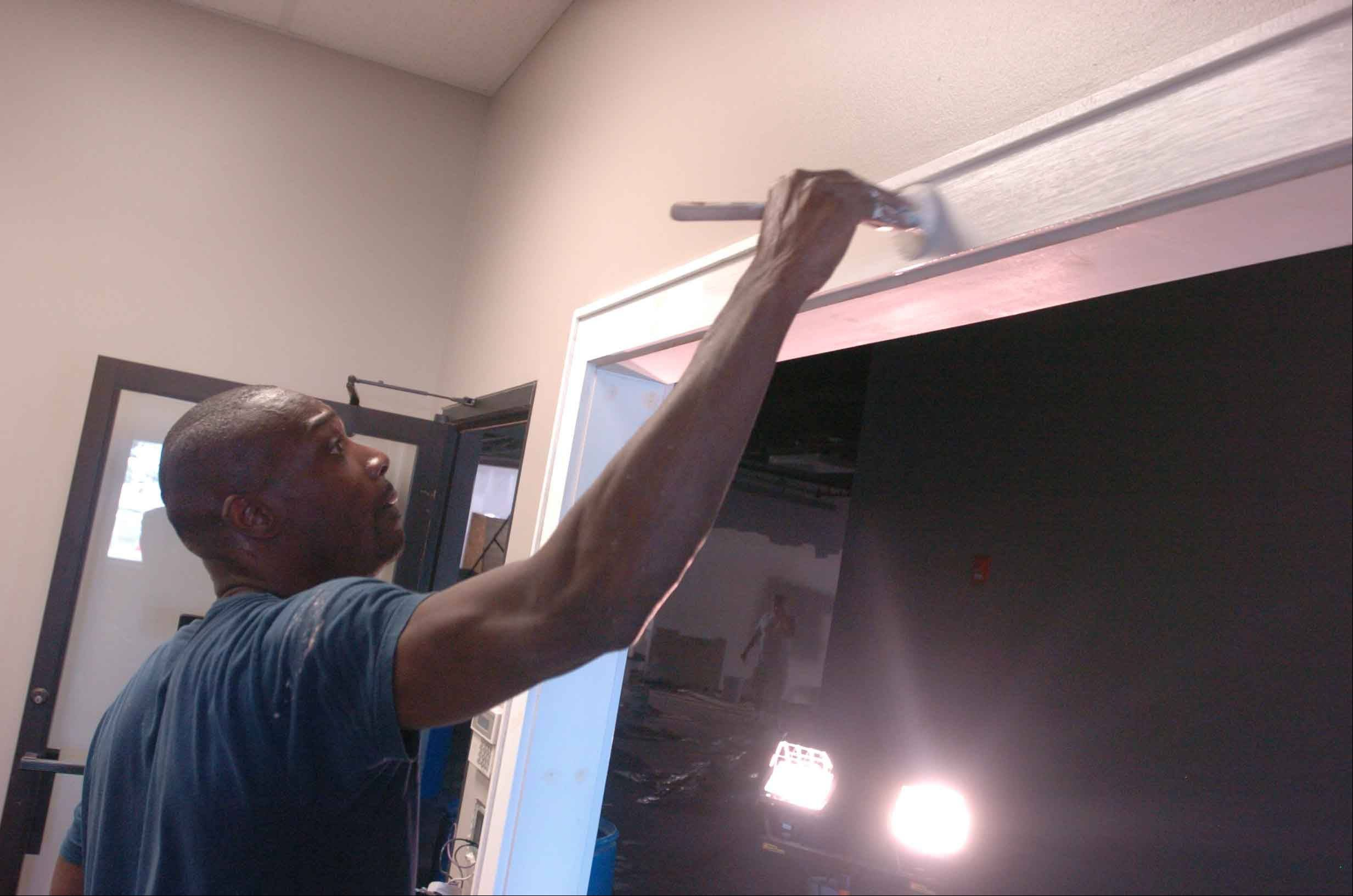 John McCulloush paints the box office at The Comedy Shrine in Aurora. Crews also painted over a unicorn to give one of the theaters its black box appearance.